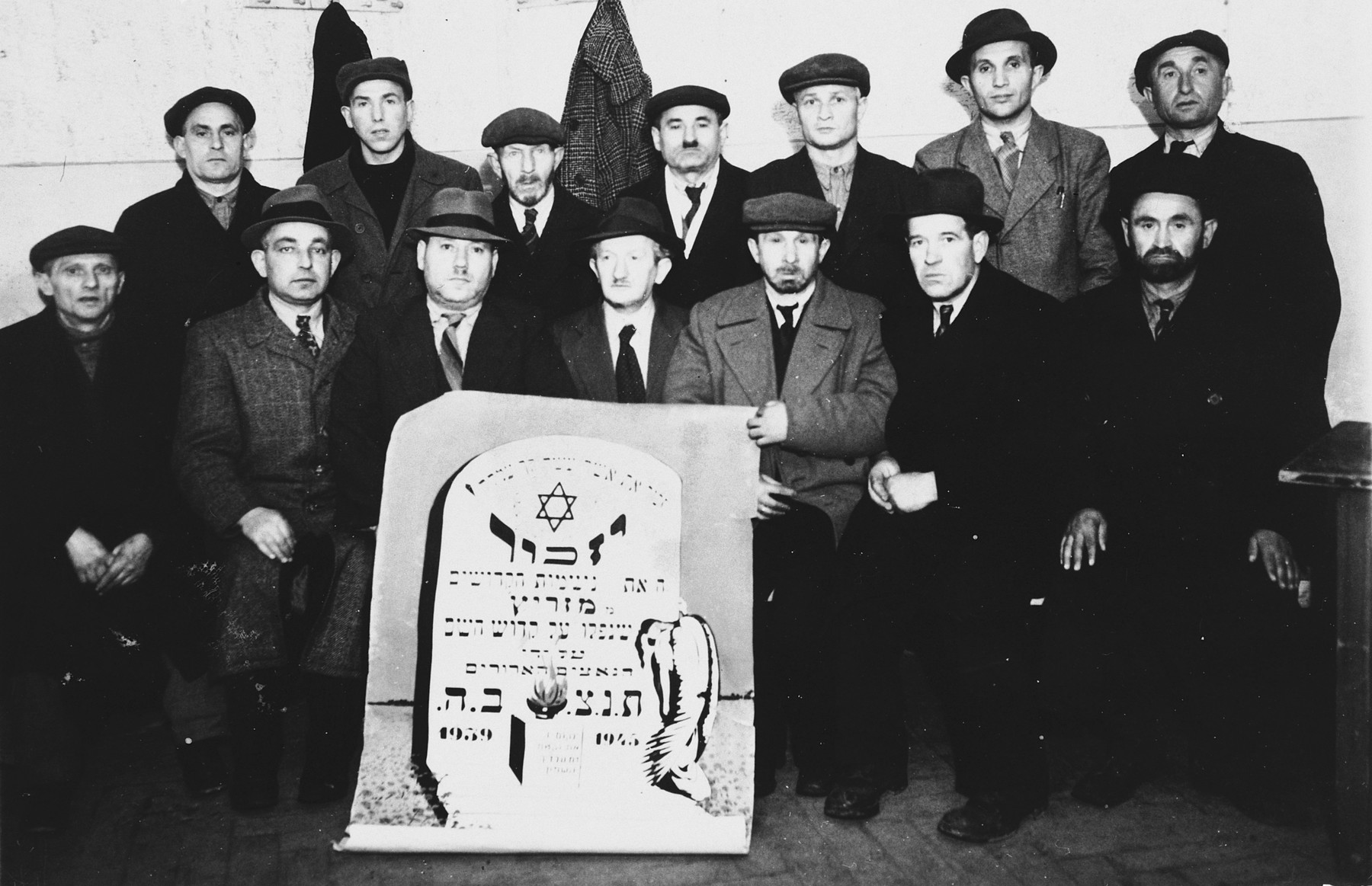 Jewish DPs gather around a memorial scroll designed to look like a  tombstone during a service to commemorate the Holocaust victims from Miedzyrzec Podlaski.  Among those pictured is Cantor Pinchos Rabinowitz who officiated at the service.