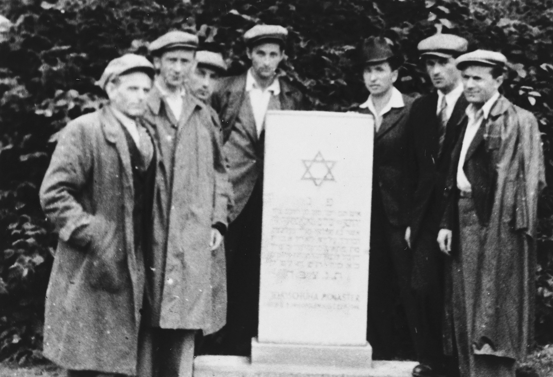 Seven Jewish DPs pose next to a memorial to the victims of the Holocaust.