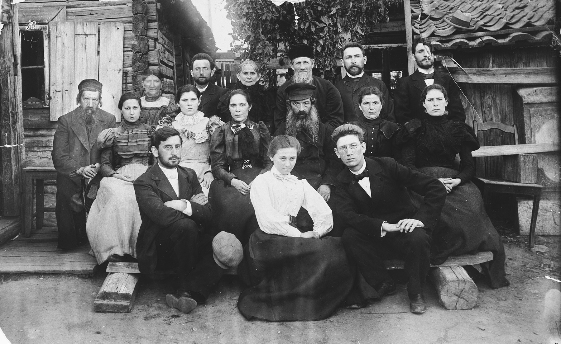 Portrait of the Magid family in front of their home in Snipishok, on the outskirts of Vilna.    Pictured is Abram (Dov Ber) Magid (bottom row, right) with his sisters Tzivia, Rivka, Rachel and Esther, and other relatives.