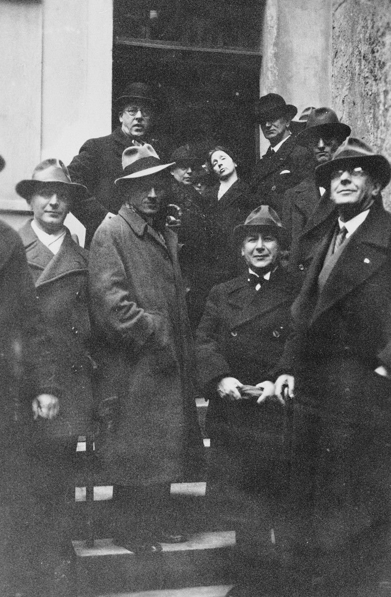 A group of men [supposedly members of the Jewish Kulturbund orchestra] pose on the steps of a building.