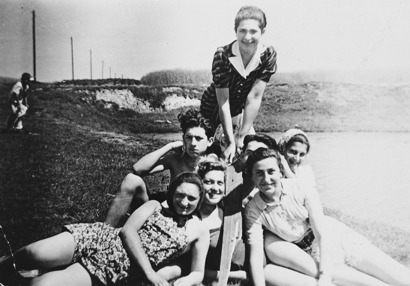A group of teenagers pose in their bathing suits during a celebration in the Bedzin ghetto to mark their high school graduation.  All had been students in the Furstenberg gymnasium, and they continued their studies clandestinely after the school was forced to close.  Pictured from left to right are (front row) Genia Prawer, Mirka Szenfeld, and Duda Rynska;   (middle row) Bobo Graubart, Heniek Lewin, and Hanka Lewin;  (standing) Ruta Rudoler.