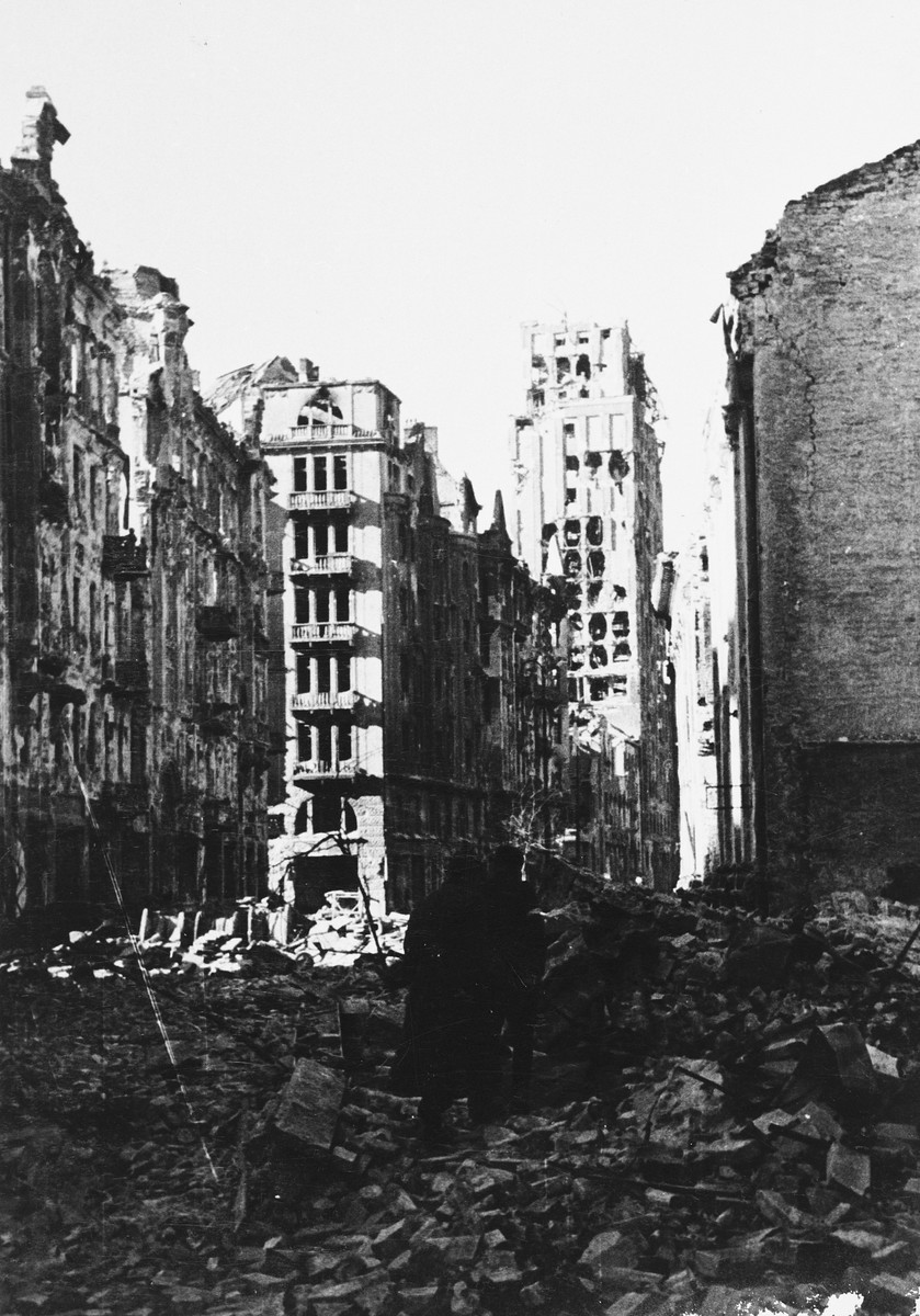 Poles make their way along a rubble strewn street during the siege of Warsaw.