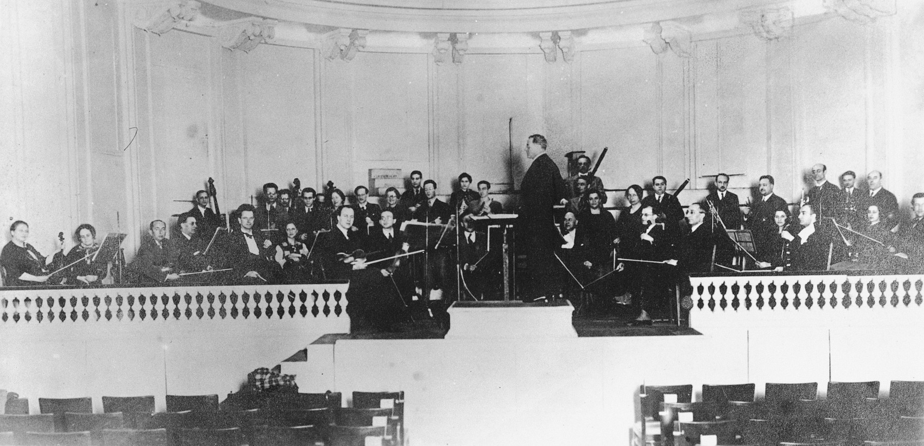 Conductor Julius Prüwer stands in from of theJewish Kulturbund orchestra on stage in Frankfurt.