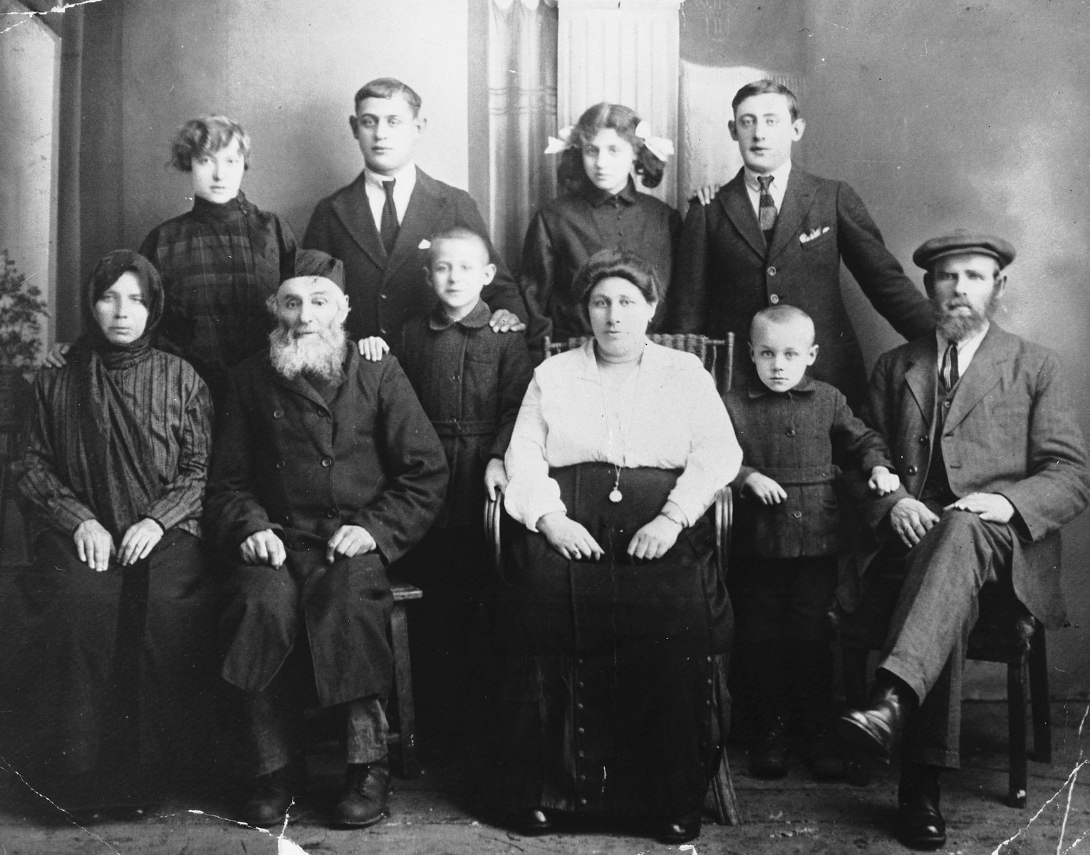 Studio portrait of the extended Fleisher family of Kursenai Lithuania.  Front left to right: great-aunt of the donor, Grandfather Shmoel-Hirsh, Reuven-Leib, Tame-Dvora (mother of donor), Yehezkel and Shlomo David Fleisher (father of donor).  Back row: Batia Michaele, Zalman Lezer, Esther Raize and Haim Ber Fleisher.