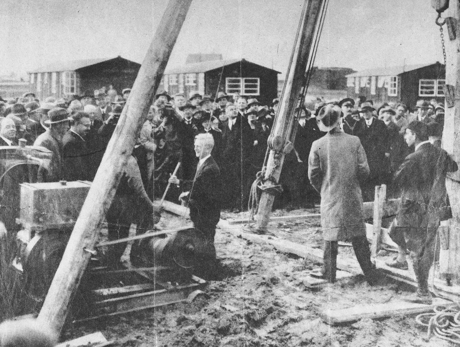"""Photo clipping from the New York Times, Photogravure Picture Section, October 21, 1934, depicting James G. McDonald, League of Nations High Commissioner on Refugees, attending a groundbreaking ceremony on October 3, for a new village, Werkdorp Wieningemeer, on the Zuyder Zee in the Netherlands.  The original New York Times caption reads: """"Holland offers asylum to the exiles from Germany: James G. McDonald, High Commissioner of the League of Nations for German Refugees, drives the first pile into the ground as work starts on a new village to be built on land reclaimed from the Zuyder Zee."""""""