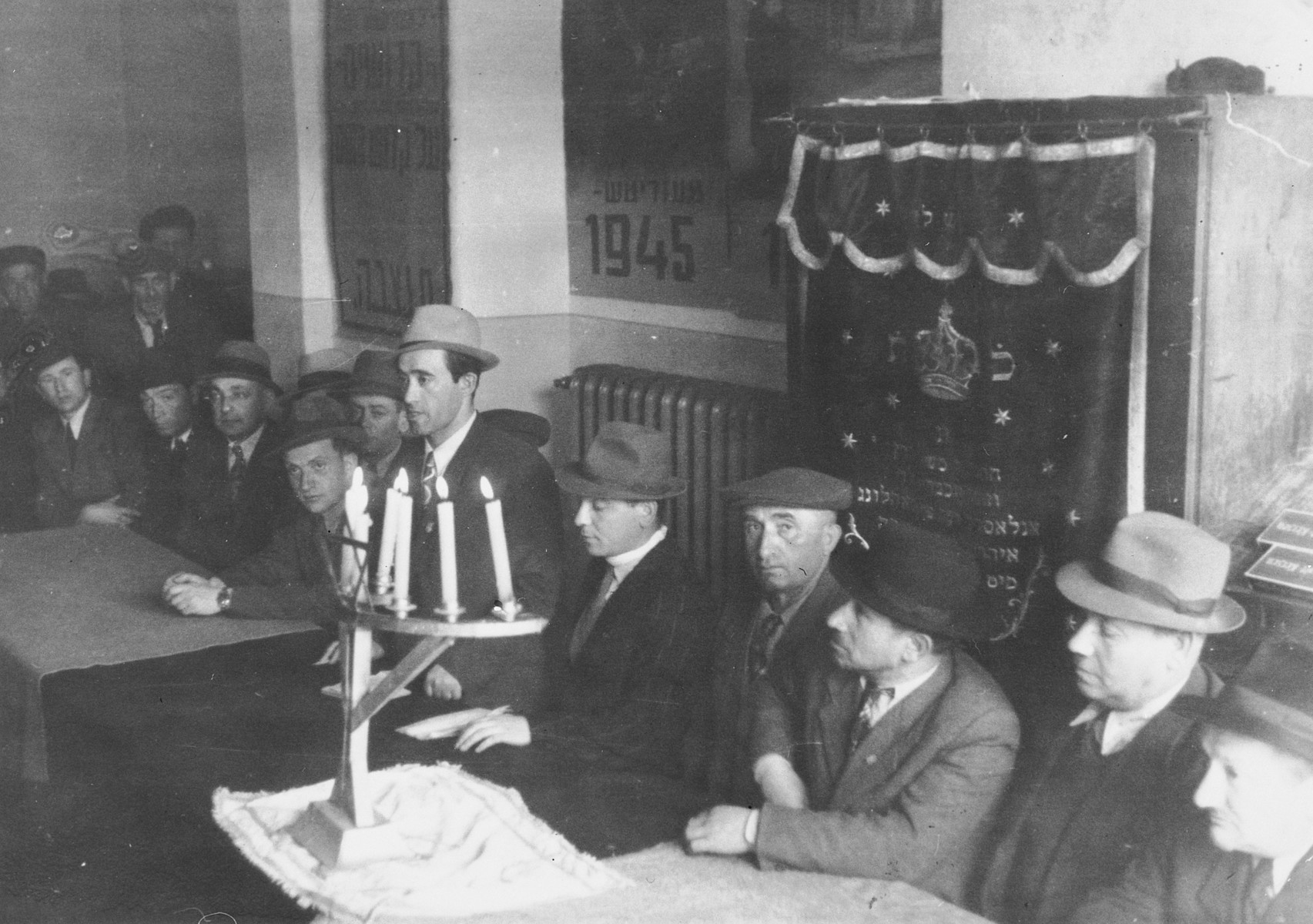Jewish DPs gather for a memorial service in the Hasenhecke DP camp synagogue in front of the torah ark and a lit menorah.