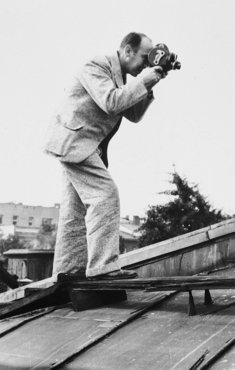 American photographer Julien Bryan films a scene from a rooftop in Warsaw during the siege of the Polish capital.
