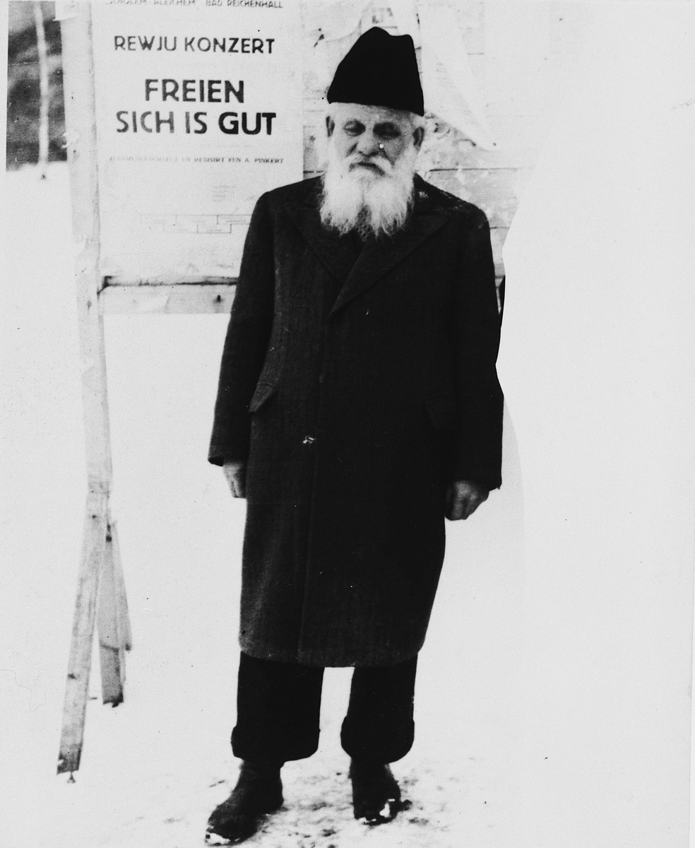 "An elderly Jewish man stands next to a sign in the Hasenecke DP camp that reads, ""Review Concert -- It's Good to be Happy."""