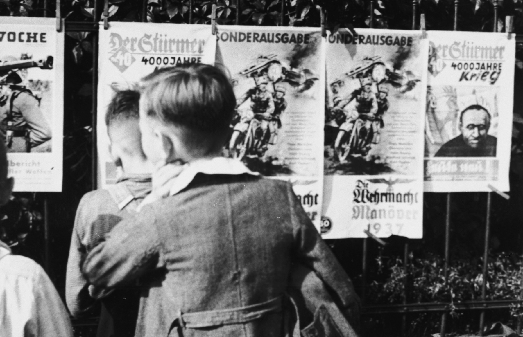 "A group of young German boys view ""Der Stuermer,"" ""Die Woche,"" and other propaganda posters that are posted on a fence in Berlin."