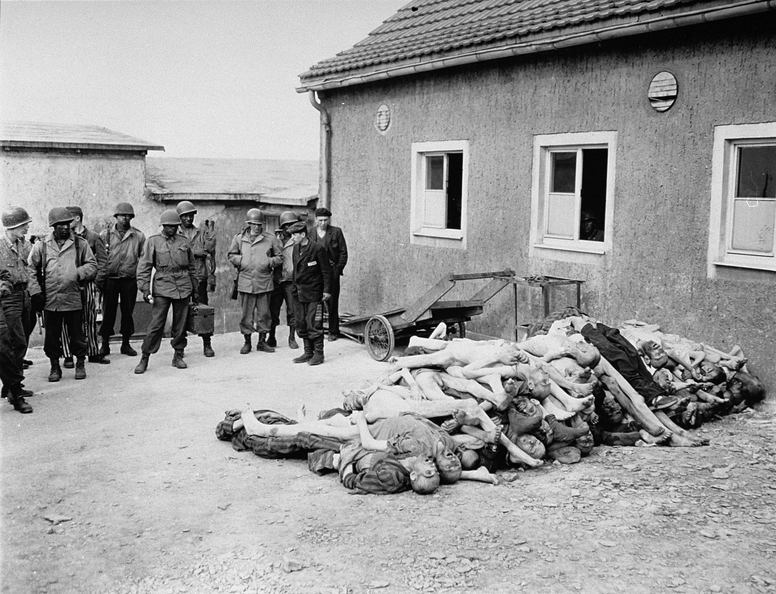 American troops, including African-American soldiers from the Headquarters and Service Company of the 183rd Engineer Combat Battalion, 8th Corps, U.S. 3rd Army, view corpses stacked behind the crematorium during an inspection tour of the Buchenwald concentration camp.  [Oversized print]  Among those pictured is Leon Bass (the soldier third from left) and Glenn S. McCrory (first, on the left).