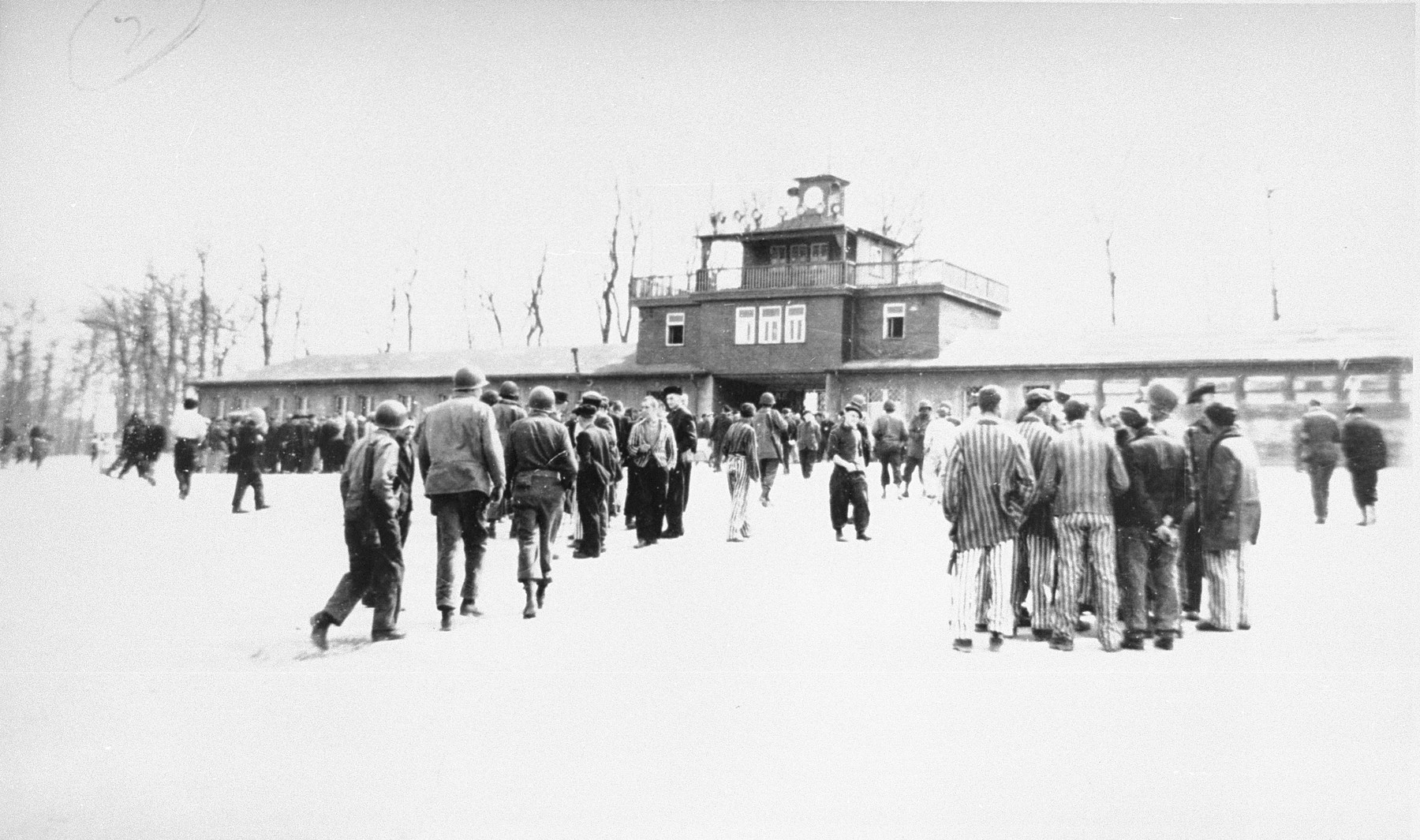 American soldiers and liberated prisoners on the Appellplatz (central plaza) of Buchenwald, behind the entrance of the camp.