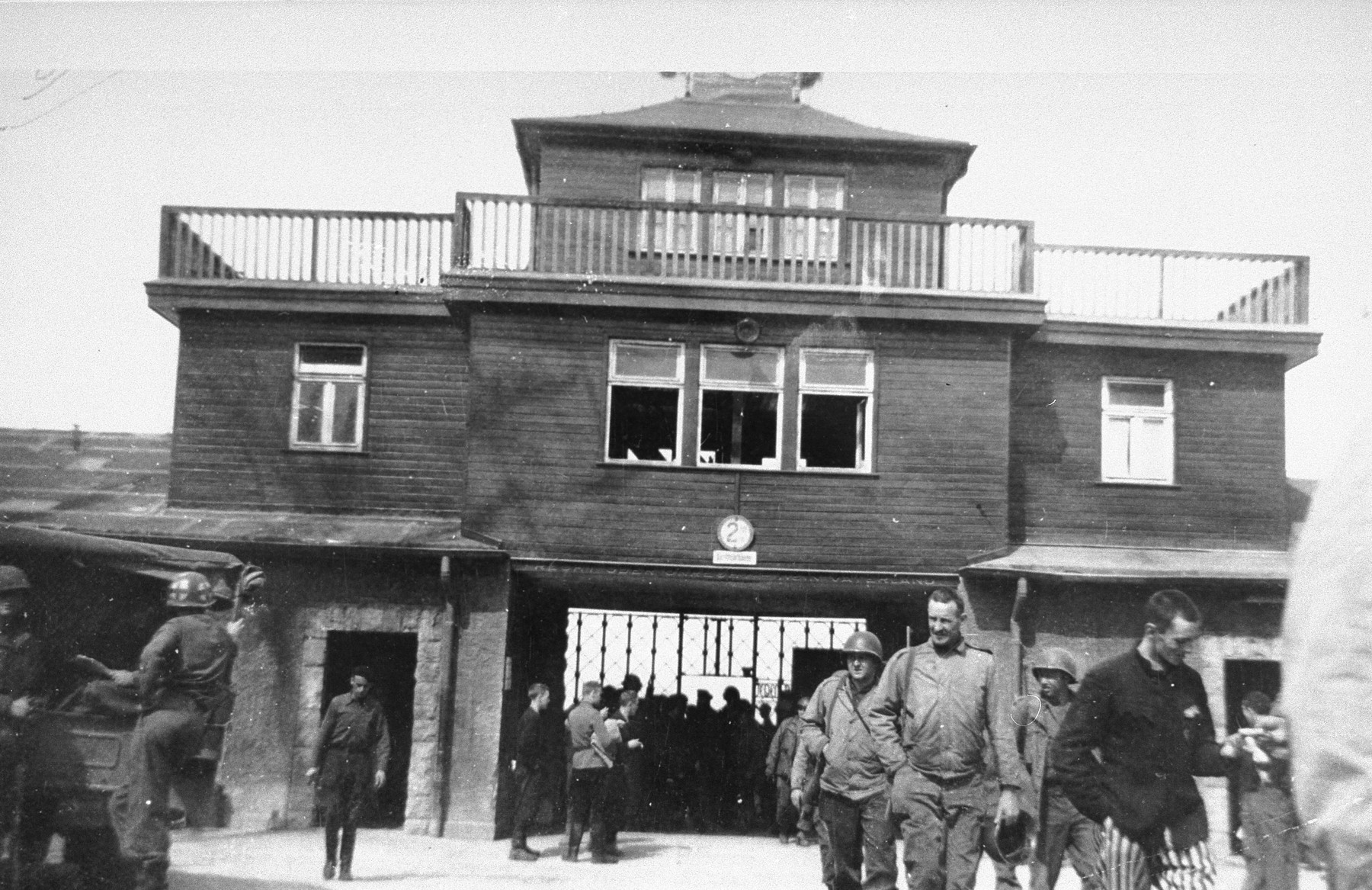American troops and survivors walk in front of the main gate of the Buchenwald concentration camp.