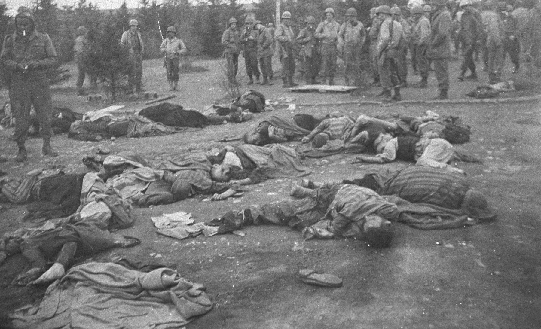 American soldiers view the corpses of prisoners that are strewn over the ground during an inspection of the newly liberated Ohrdruf concentration camp.
