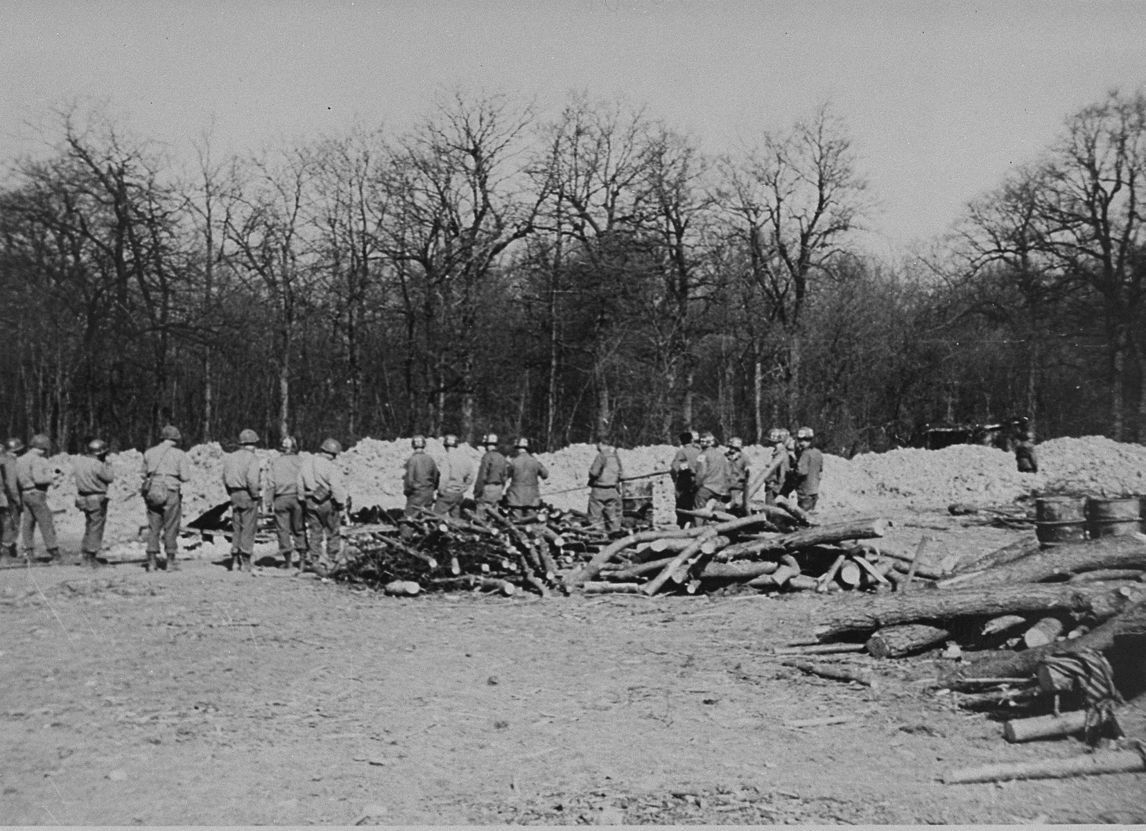 American soldiers examine the charred remains of corpses hastily burned during the evacuation of the Ohrdruf concentration camp.  The mounds of dirt in the distance mark a mass grave.
