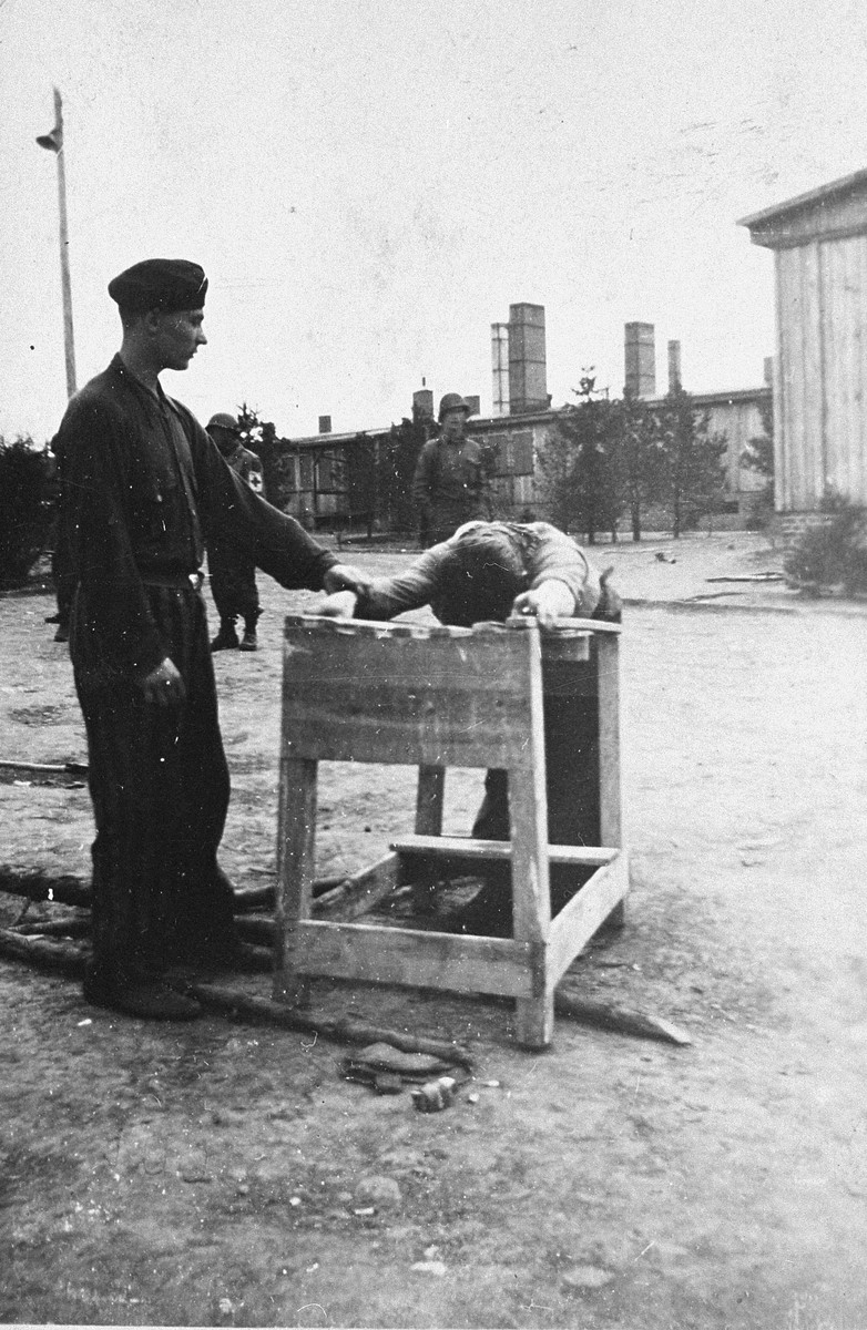 A survivor demonstrates methods of torture used by guards at the Ohrdruf concentration camp to American soldiers