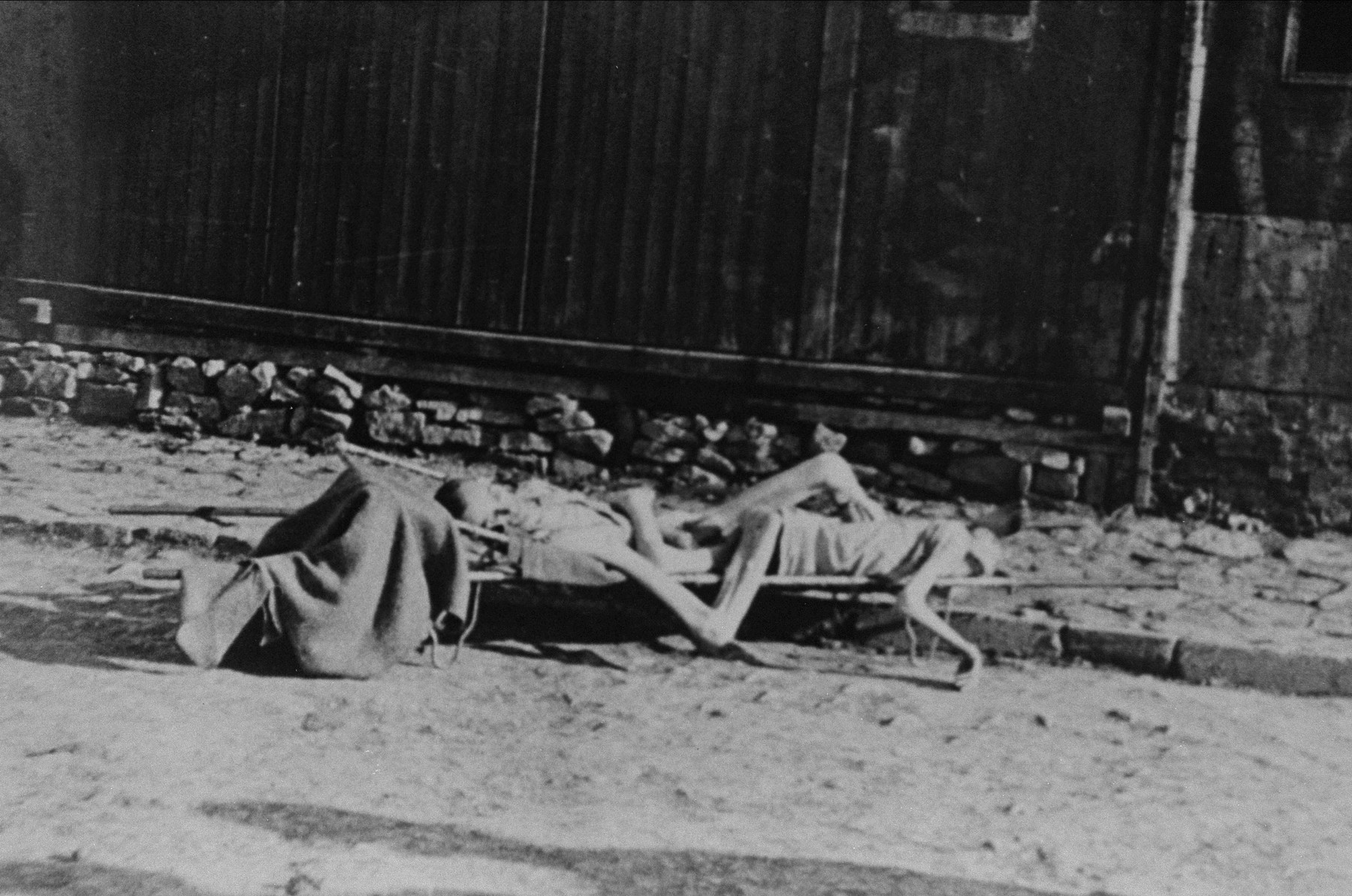 Two corpses on a stretcher in front of a barracks awaiting burial.