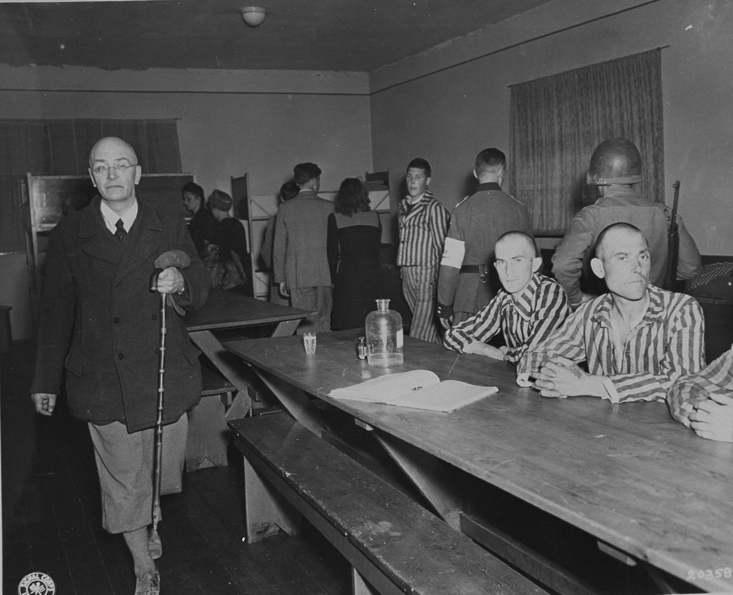 German civilians from Weimar under American military guard are forced to see the starved victims of Nazi brutality in Buchenwald.