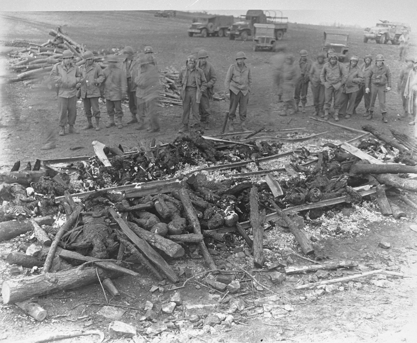 "While on an inspection tour of the newly liberated Ohrdruf concentration camp, American soldiers view the charred remains of prisoners that were burned upon a section of railroad track during the evacuation of the camp.  The original caption reads ""The charred remains of burned prisoners are shown shortly after capture of the area by Third U.S. Army troops.  The Nazis exhumed and burned 1,606 murdered victims in six days in an attempt to destroy the evidence on orders from higher headquarters.""  Among those pictured are George Stantis (second from left, tentative identification), Jack Caminer (fifth from left with goggles), a German-Jewish immigrant, who served in military intelligence, and Staff Sergeant  Maynard B. Cohen or Americo Venuto is eighth from the left, standing alone in the middle.   Captain Ralph Kopansky is pictured on the far right, with a camera around his neck."