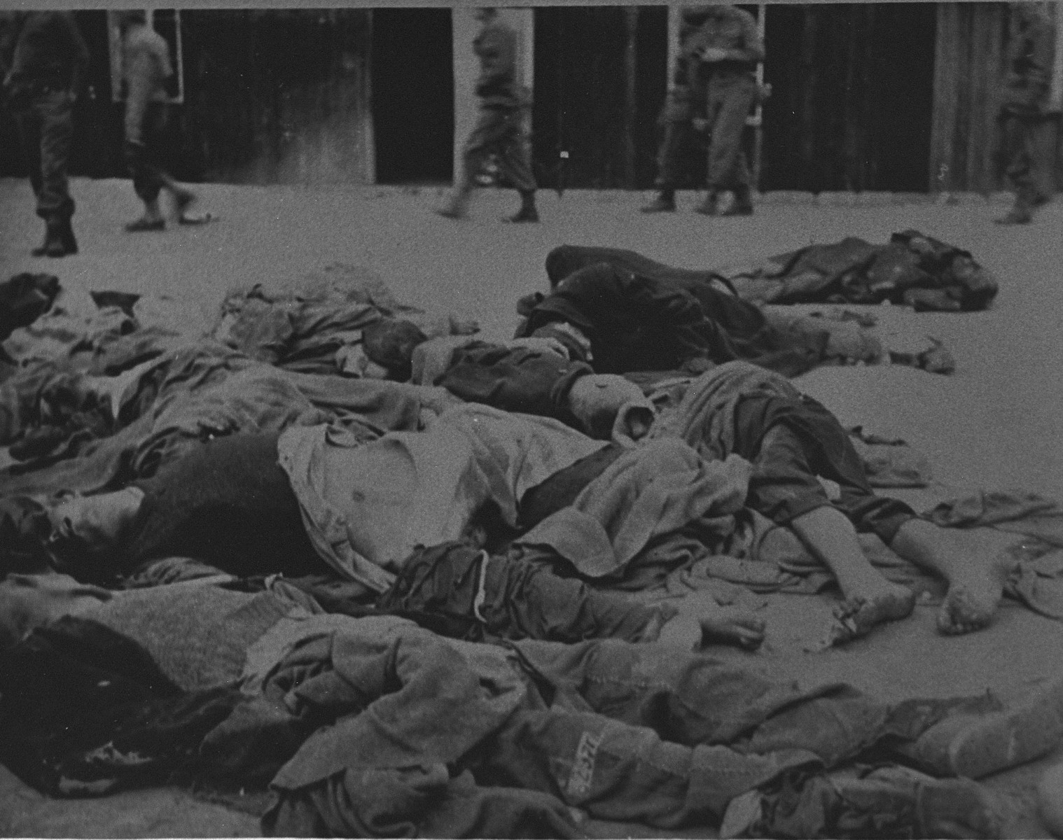 American soldiers in the background walk past corpses in Ohrdruf.