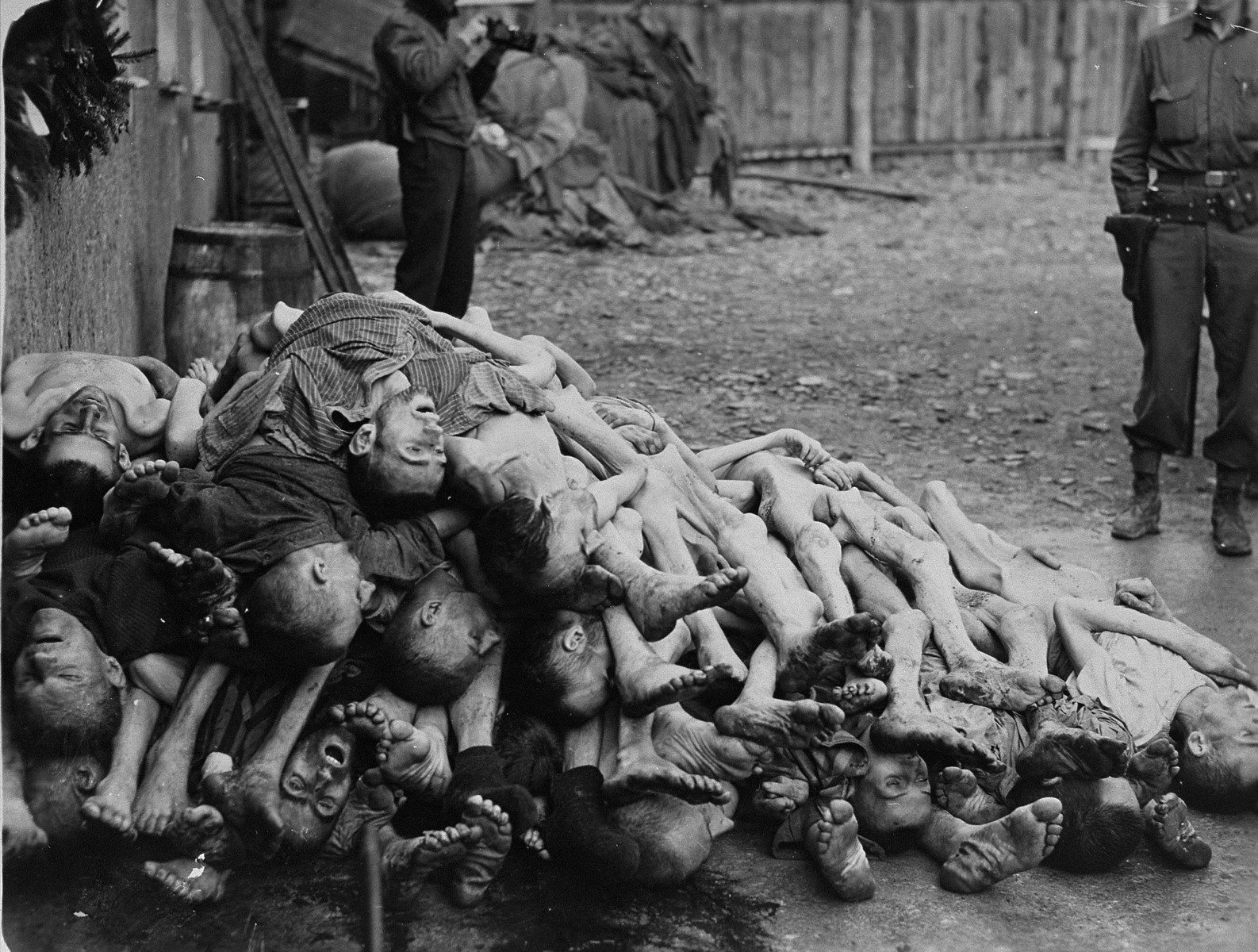 American soldiers view a pile of corpses found behind the crematorium in the newly liberated Buchenwald concentration camp.