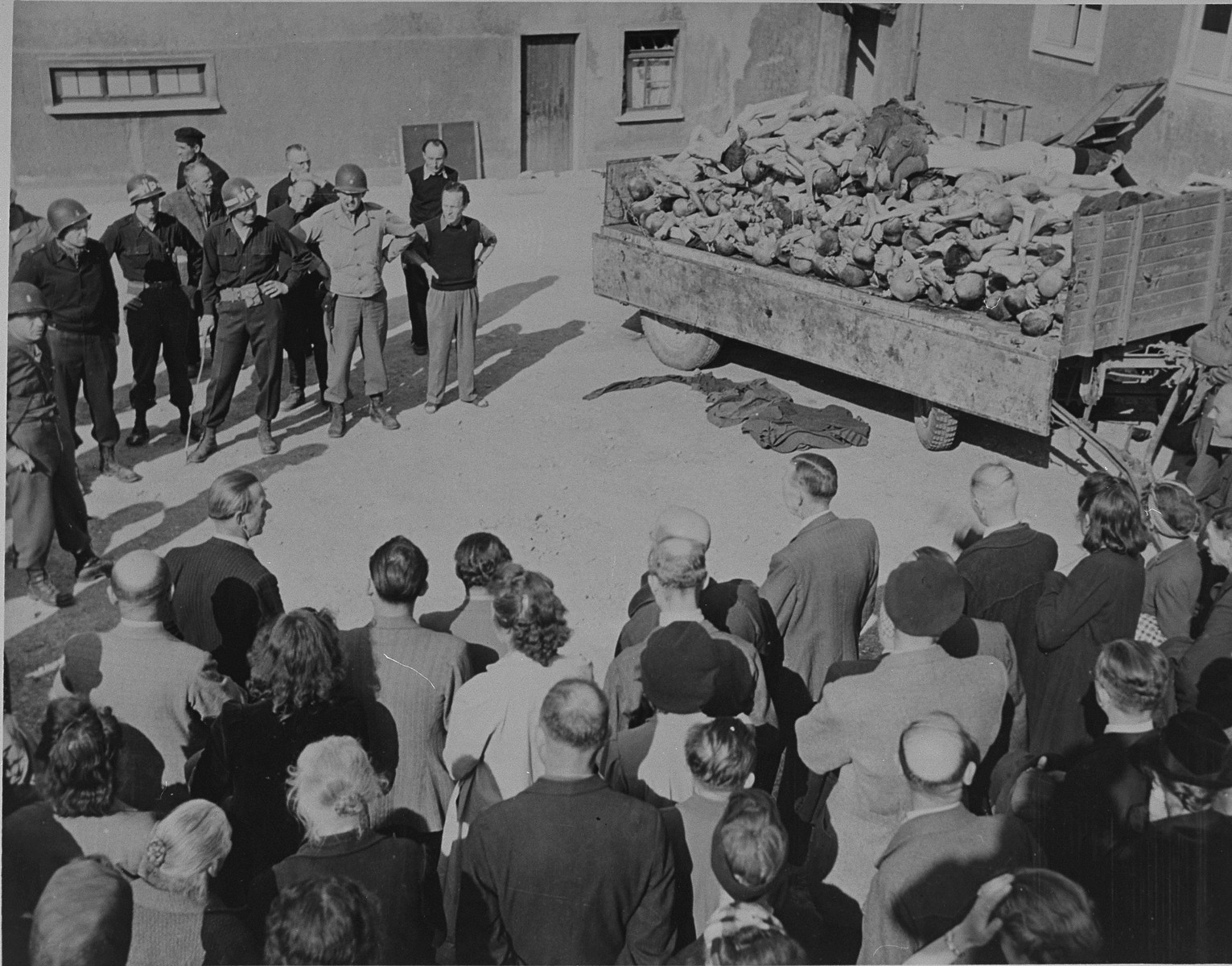 "German civilians under U.S. military escort are forced to view a wagon piled with corpses in the newly liberated Buchenwald concentration camp.  Original caption reads:  ""German civilians are forced to look at a truckload of dead Allied and political prisoners at Buchenwald camp.  Under U.S. military escort, the civilians were forced to view all the evidence of atrocities in the camp."""