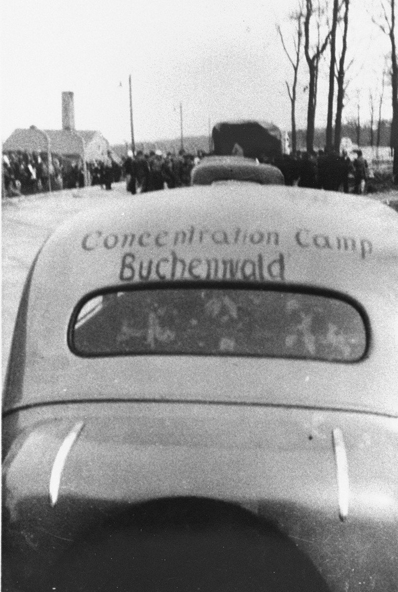 A vehicle from the International Red Cross delegation visits Buchenwald after liberation.  The words Buchenwald concentration camp are written on the back of the vehicle.
