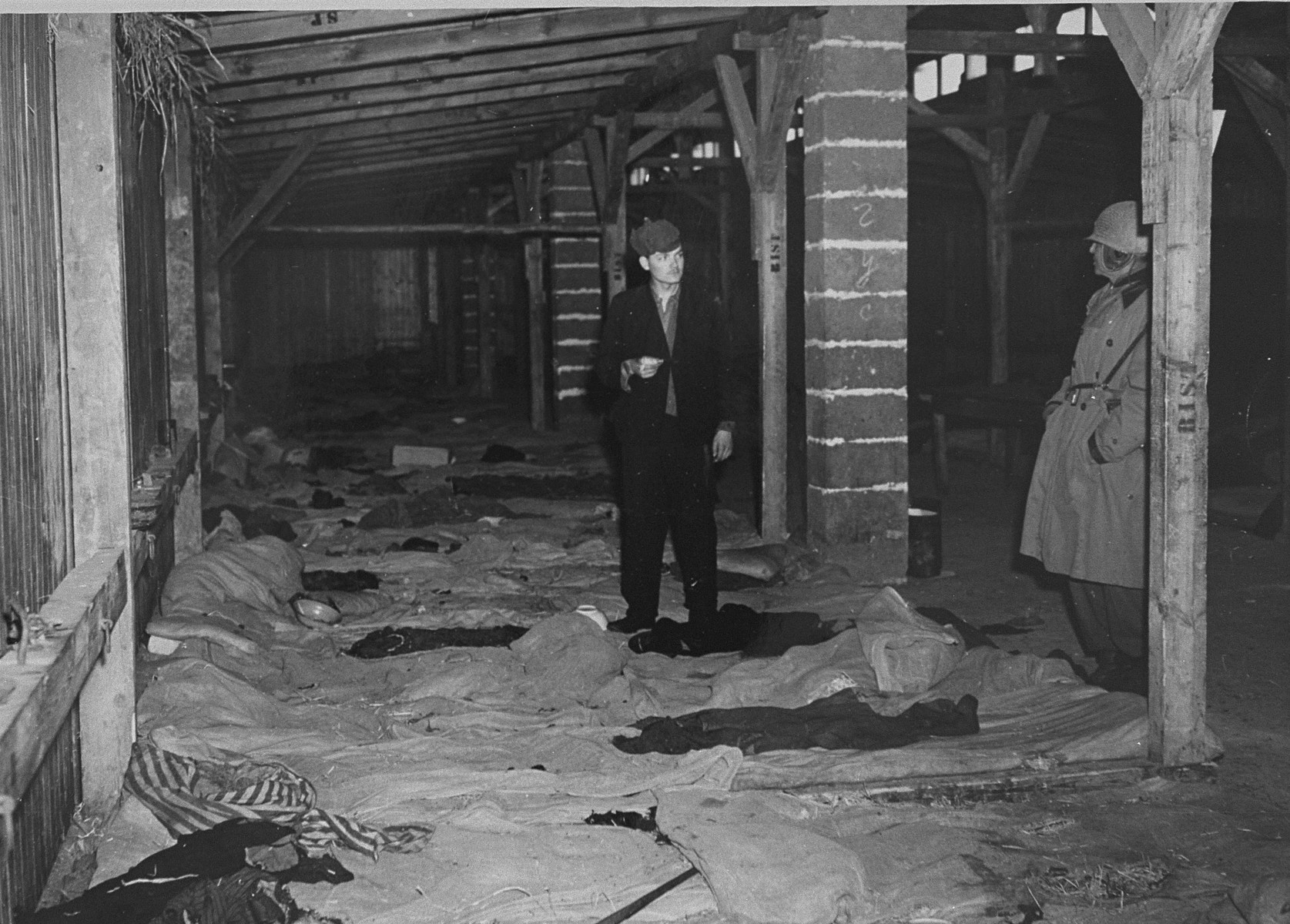 A survivor of the Ohrdruf concentration camp shows U.S. Army Colonel Hayden Sears the inside of a barracks where 196 prisoners lived.
