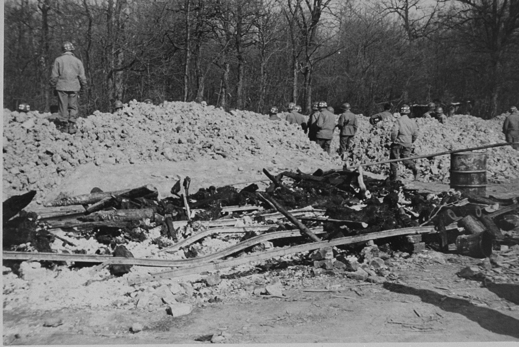 American soldiers stand at the edge of a mass grave in Ohrdruf. Behind them lie the charred remains of prisoners hastily burned during the evacuation of the camp.