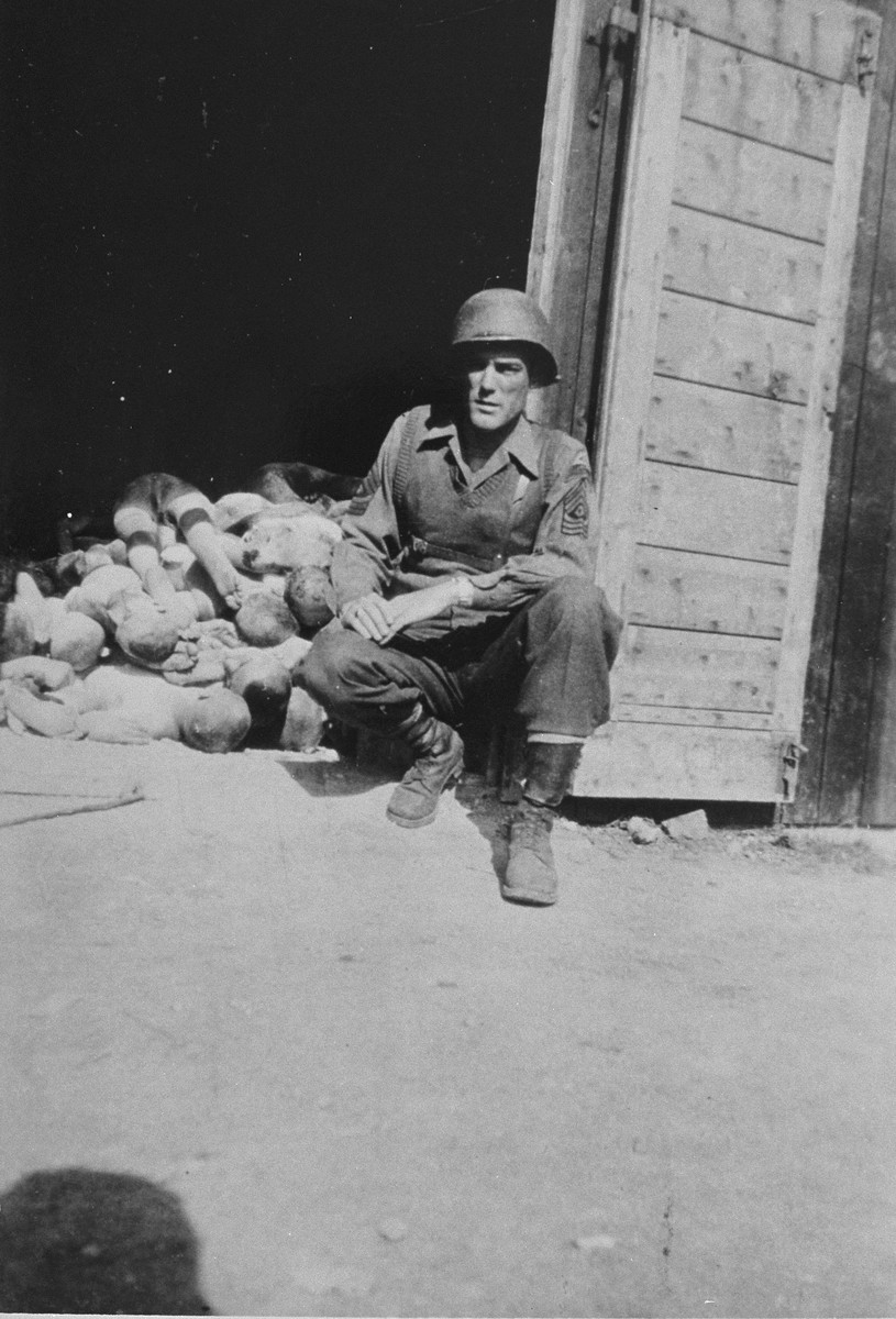 First Sergeant John H. Harris kneels in front of a pile of corpses inside a shed in the Ohrdruf concentration camp.