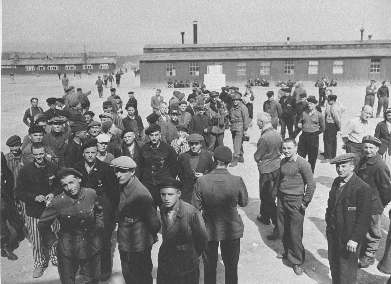 Survivors congregate in the central compound of Buchenwald along with American soldiers and journalists during an official tour of the liberated camp by an international group of radio commentators.