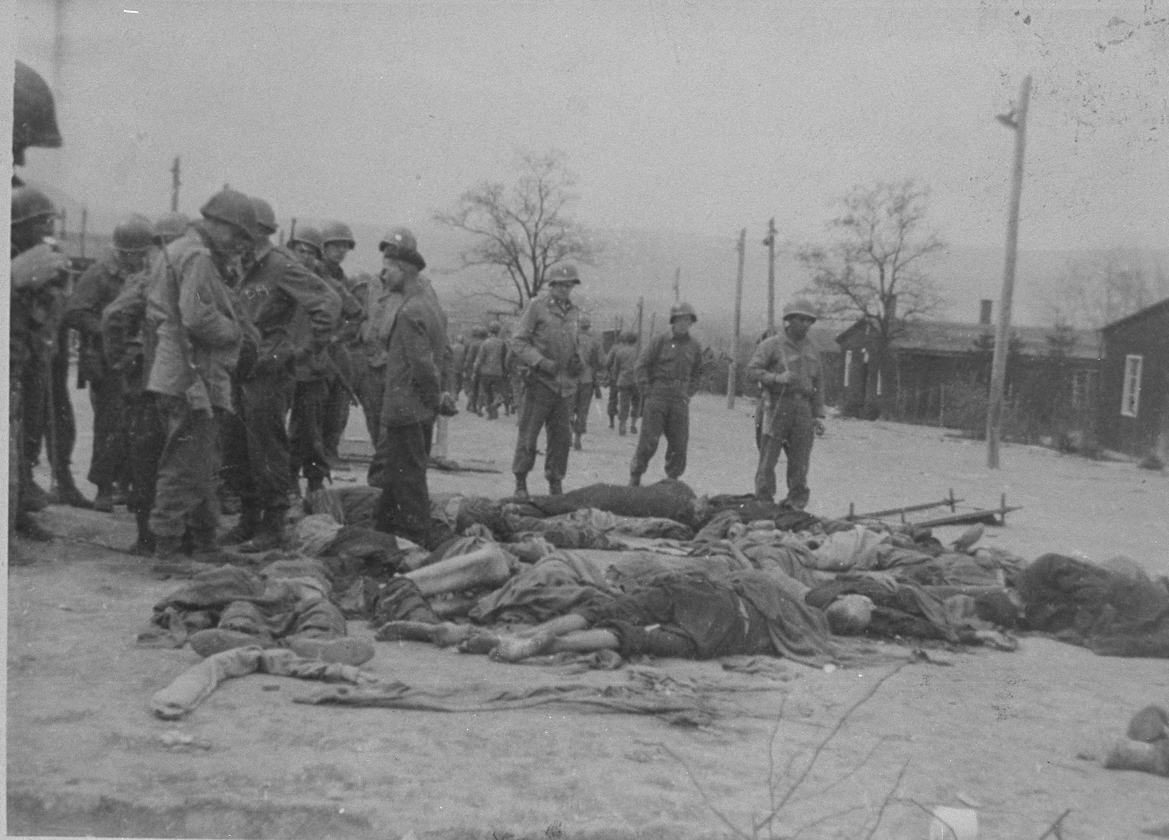 American soldiers view the bodies of prisoners shot by the SS during the evacuation of the Ohrdruf concentration camp.  The man second soldier from the right with his hands in his pockets has been identified as Willis E. Christ.