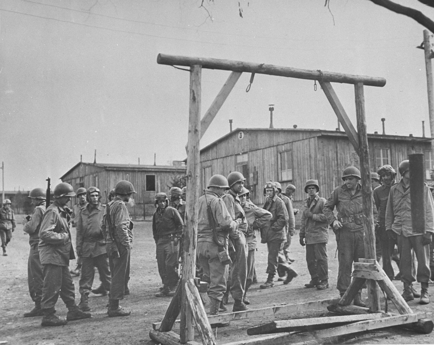 American soldiers view a gallows erected between rows of barracks in the Ohrdruf concentration camp.