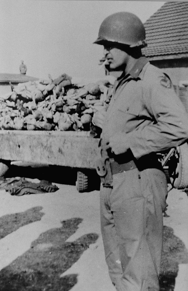 An American soldier stands in front of a wagon piled with corpses.