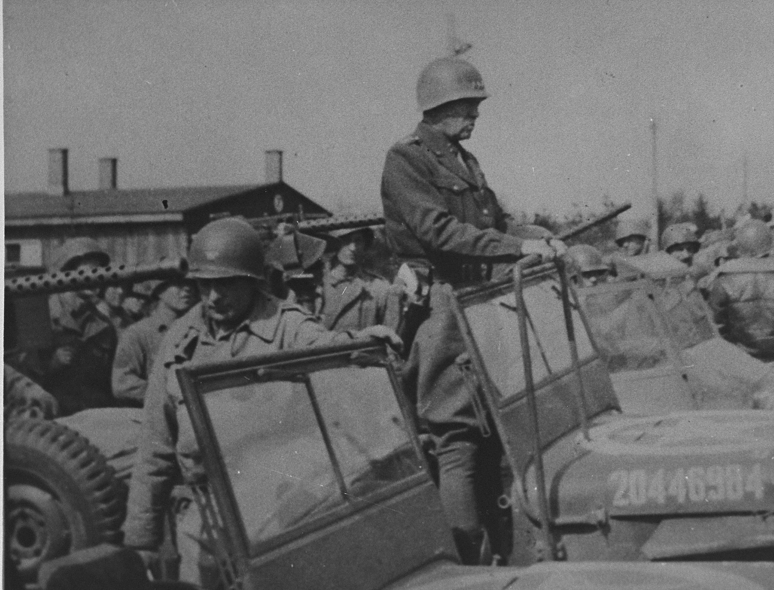 General George Patton (standing in the jeep) prepares to depart from Ohrdruf after an official tour of the newly liberated camp.