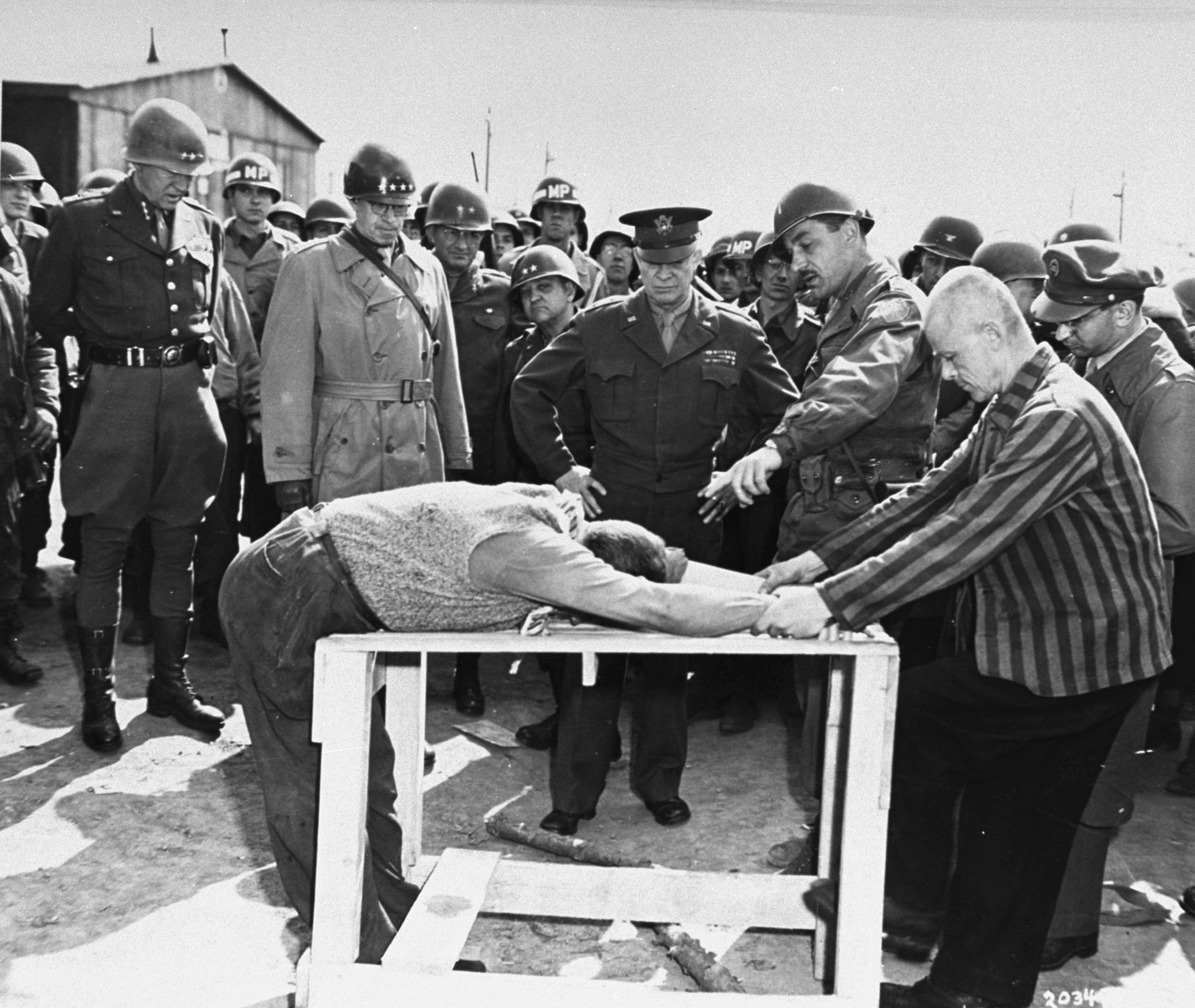 "Survivors of the Ohrdruf concentration camp demonstrate torture methods used in the camp to top ranking American generals.  Among those pictured are General Dwight Eisenhower, (center), General Omar Bradley (second from the left), and General George S. Patton (left). Jules Grad (far right), pool correspondent for the ""Stars and Stripes,"" is taking notes.  The mustached soldier who is pointing at the demonstrated torture victim is Alois J. Liethen of Appleton, WI, who served as the interpreter for the tour of Ohrdruf.   Original caption reads: ""General Dwight D. Eisenhower, supreme allied commander, watches grimly while occupants of the German Concentration Camp at Gotha demonstrate how they were tortured by the Nazi sadists operating the camp.  General ""Ike"" visited the camp during a tour of the Third Army Front.  General Omar N. Bradley, 12th Army Group CG, and Lt. General George S. Patton, 3rd Army CG, are at the supreme commander's right.""  Original caption from donated photograph reads:  ""General of the Army Dwight D. Eisenhower (center), Supreme Commander-in-Cheif Allied Expeditionary Force, watches grimly as liberated slave workers of the concentration camp at Ohrdnuf, Germany, demonstrated how they were tortured by their guards.  Lieutenant General George S. Patton, Jr., Commander of the Third U.S. Army, stands at left and next to him is General Omar N. Bradley, Commander of teh 12th Army Group."""