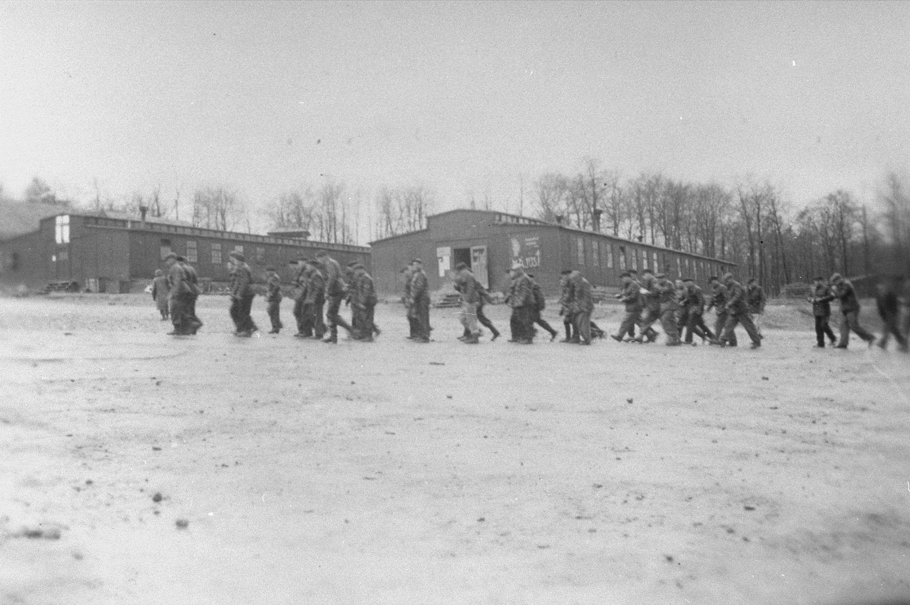 German civilians march toward a barracks to collect bodies for burial.