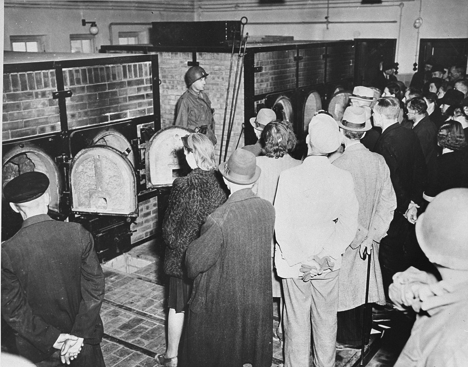 Civilians from nearby Weimar are forced by American soldiers to see the remains of prisoners in the crematorium ovens of Buchenwald during their tour of the concentration camp.