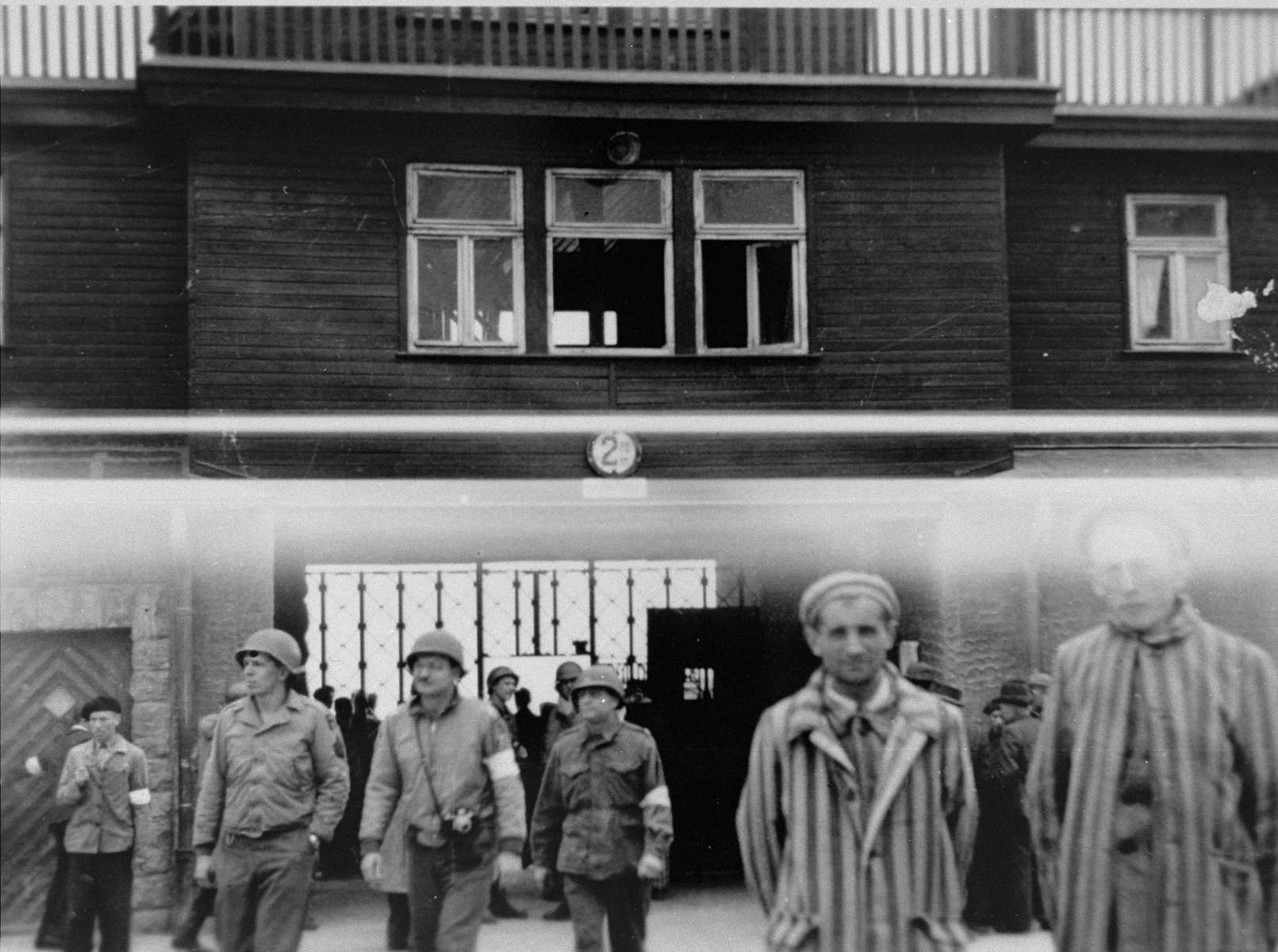 American soldiers and survivors stand by the entrance of Buchenwald.