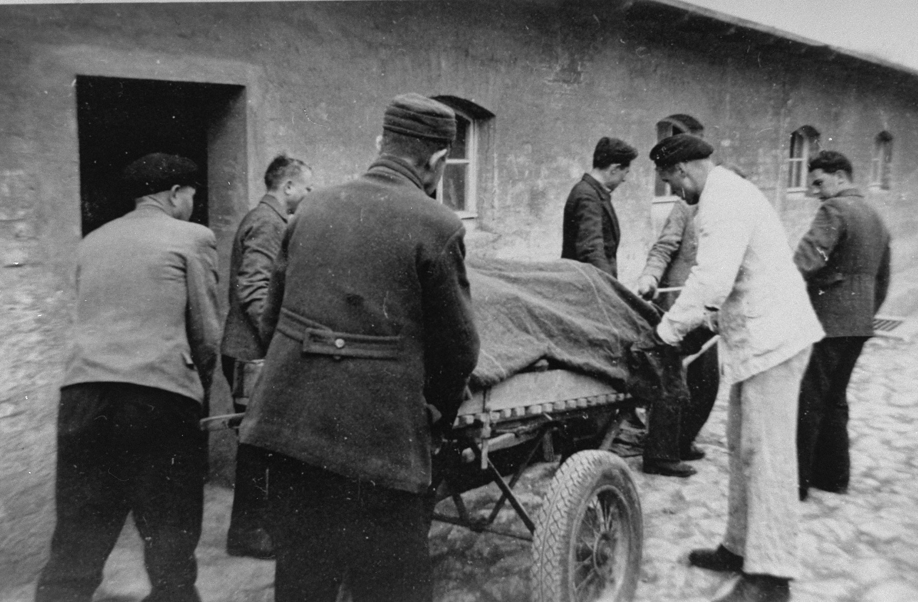 German civilians push a cartful of corpses at Buchenwald after liberation.