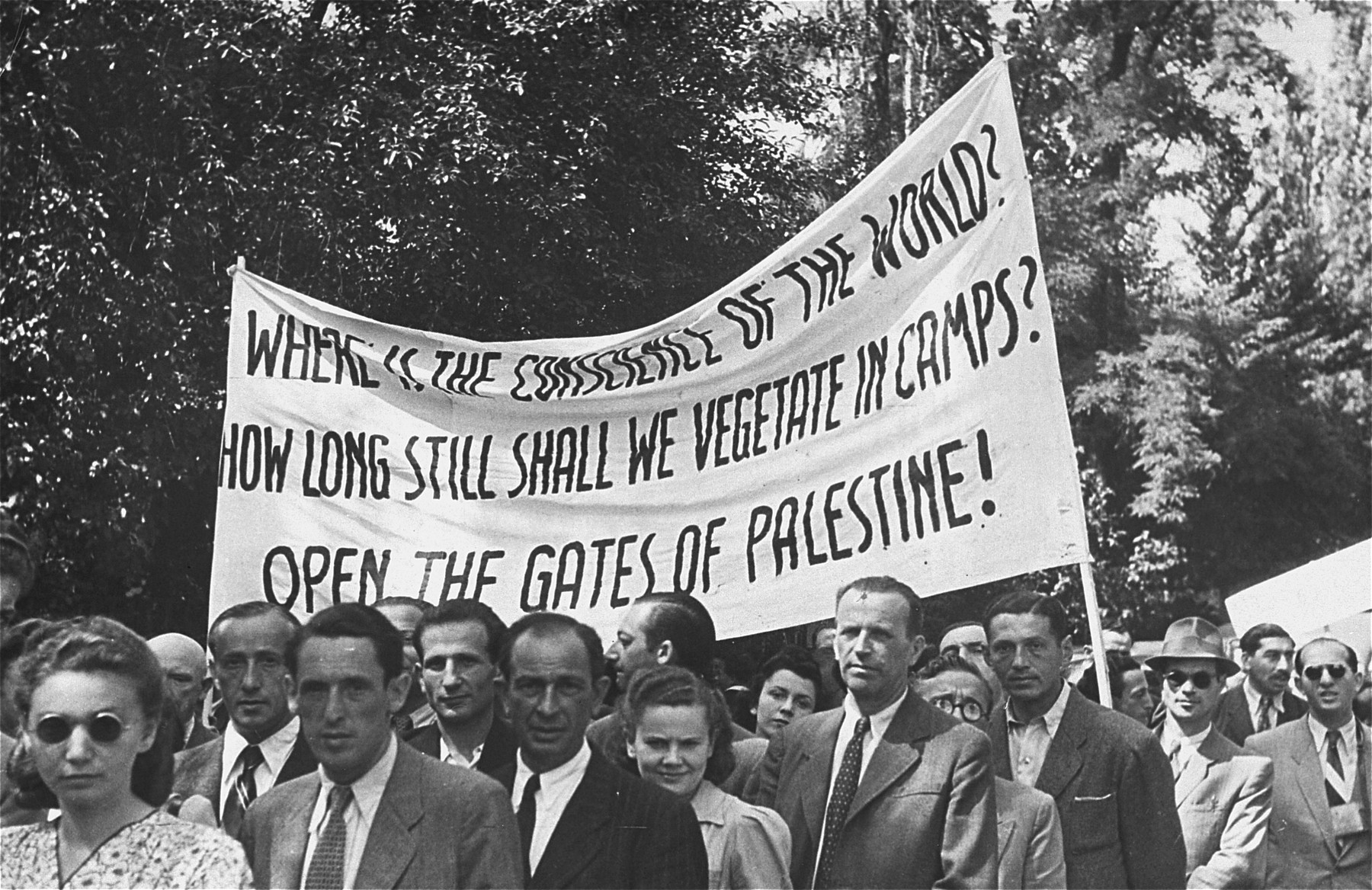 Jewish DPs protest British immigration policy to Palestine at the Mittenwald displaced persons camp and to commemorate the death march from Dachau to Tyrol.  They stand beneath a banner in English demanding that the British open the gates to Palestine.