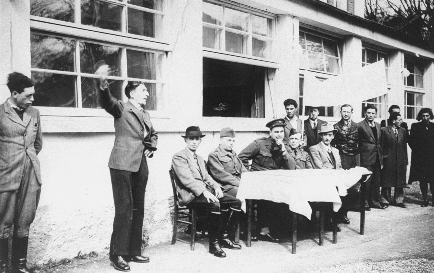 Jewish DPs in the Mittenwald displaced persons camp conduct a meeting at which they protest British immigration policy to Palestine while they commemorate the death march from Dachau to Tyrol.  Among the participants is Mr. Spier, an UNRRA representative.