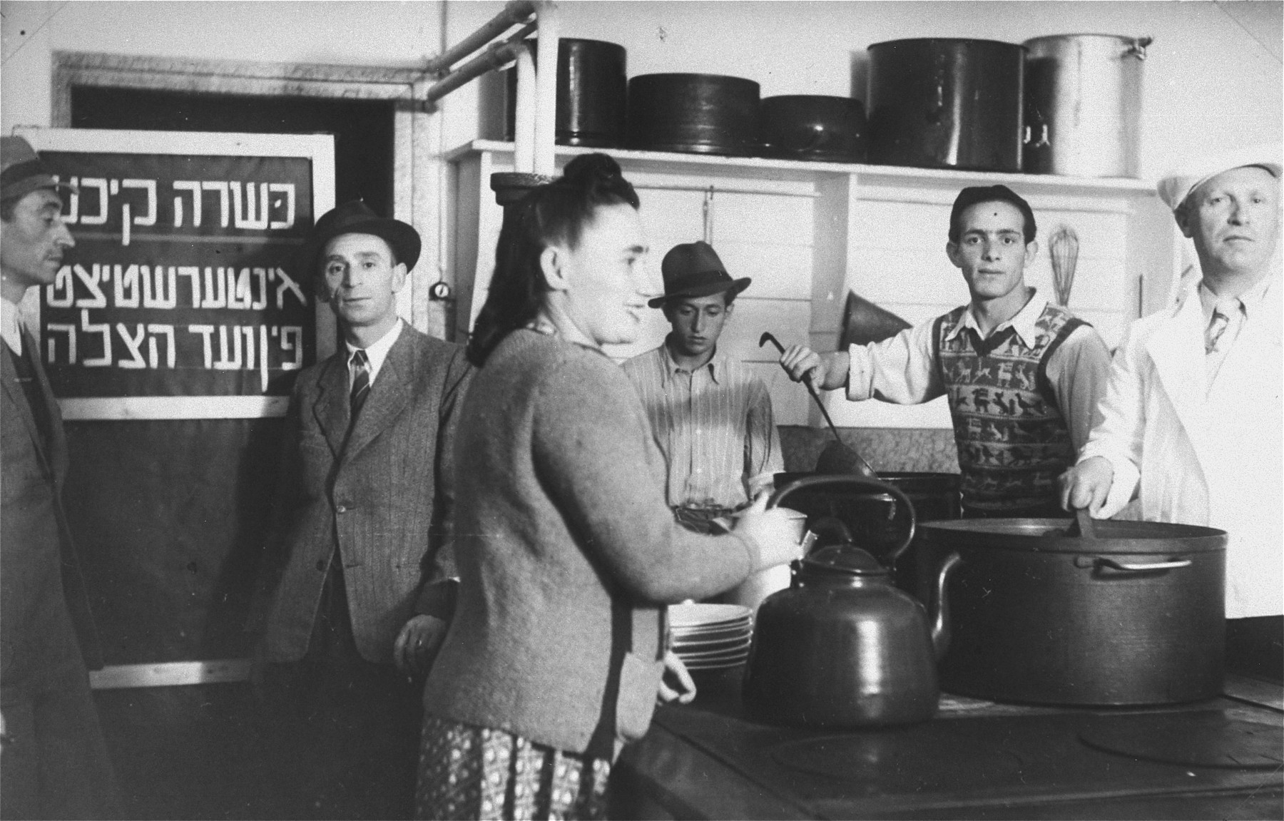 """Jewish DPs at work in the kosher kitchen at the Mittenwald displaced persons camp.    The Yiddish sign on the door reads: """"Kosher kitchen, underwritten by the Vaad Hatzala [Rescue Committee]."""