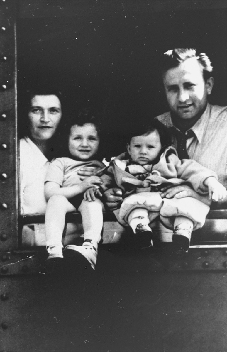 A Jewish DP family poses in the window of a train as they depart from Germany on the first leg of their journey to the U.S.  Pictured from left to right are: Sabina (Kramer) Milman, Estera Milman, Isa Milman, and Eljasz Milman. The family had spent time previously in the Schwaebisch Hall and Heidenheim DP camps.
