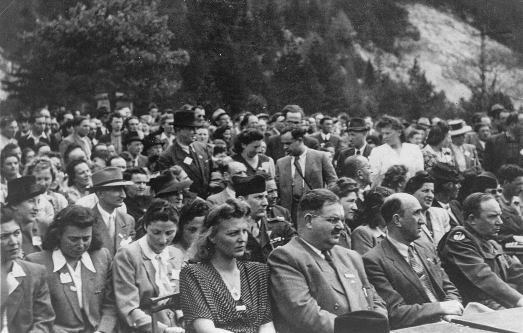 View of the audience at an outdoor meeting of Jewish DPs in the American Zone of Germany held in the Mittenwald displaced persons camp to commemorate the death march from Dachau to Tyrol.   Among those pictured are the American officer serving as the liaison between the American military government and the Central Jewish Committee, and the representative of the local German government.