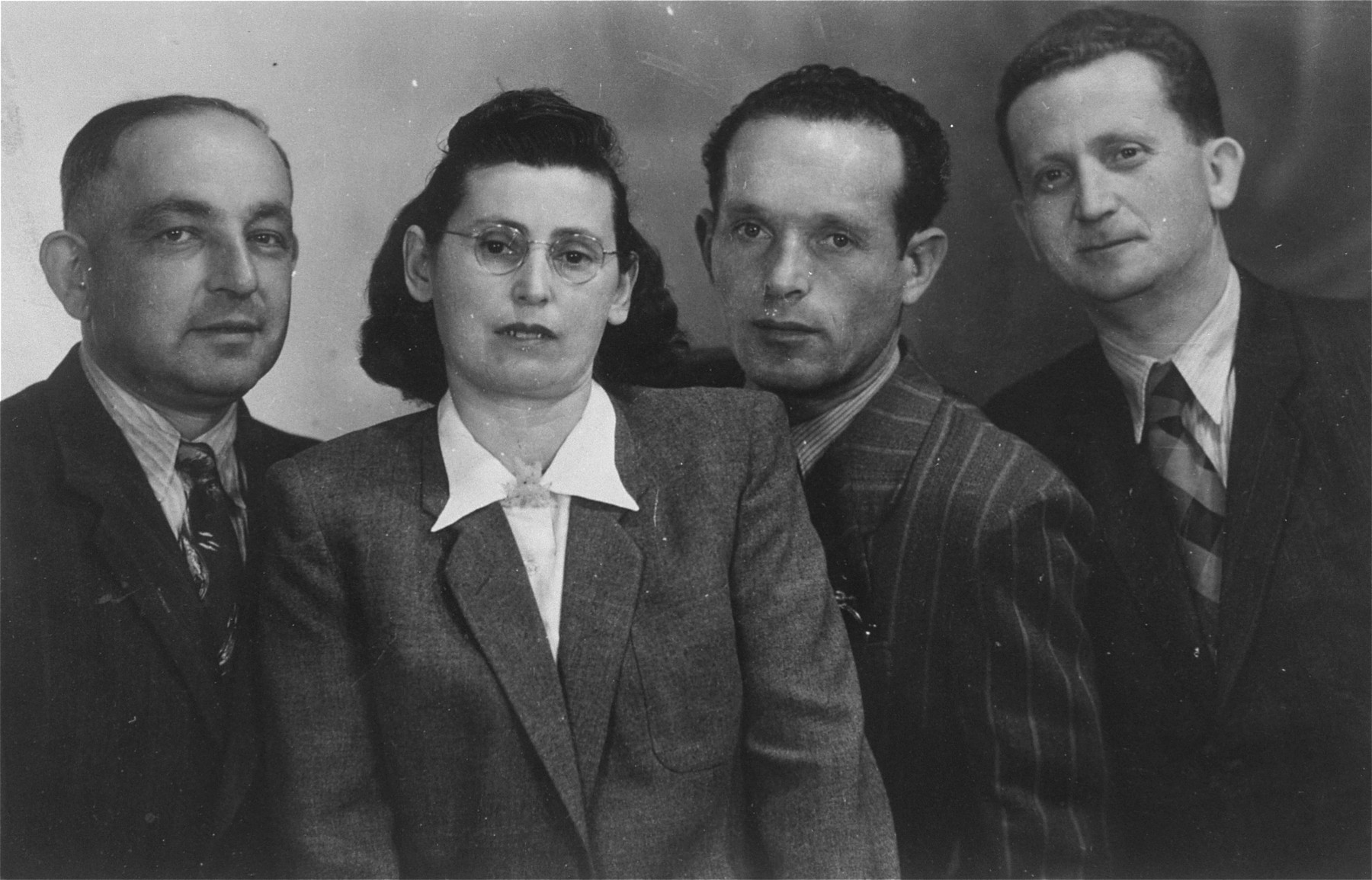 """Group portrait of four survivors, who were living as displaced persons in Germany.    Pictured from left to right are:  Motel Feldman, Pesia Friedman, Moshe Friedman, and Shalom-Yudel.  The Yiddish inscription on the back of the photo reads, """"As a momento to our dear friend Mendel Rozenblit, [from] Motel Feldman, Pesia Friedman, Moshe Friedman.  For our only surviving Lukower friend from Auschwitz and Dachau, [from] Shalom-Yudel."""""""