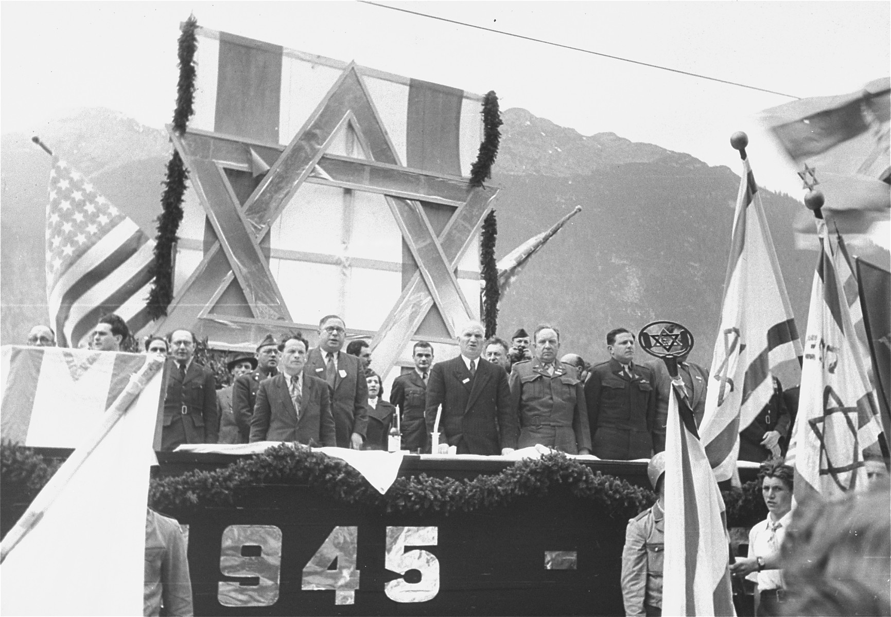 David Treger (front row, center in white hair), President of the Central Committee of the Liberated Jews in Bavaria, stands on the speakers platform with other DP leaders and official guests at a public meeting held in the Mittenwald displaced persons camp to protest British immigration policy in Palestine and to commemorate the death march from Dachau to Tyrol.