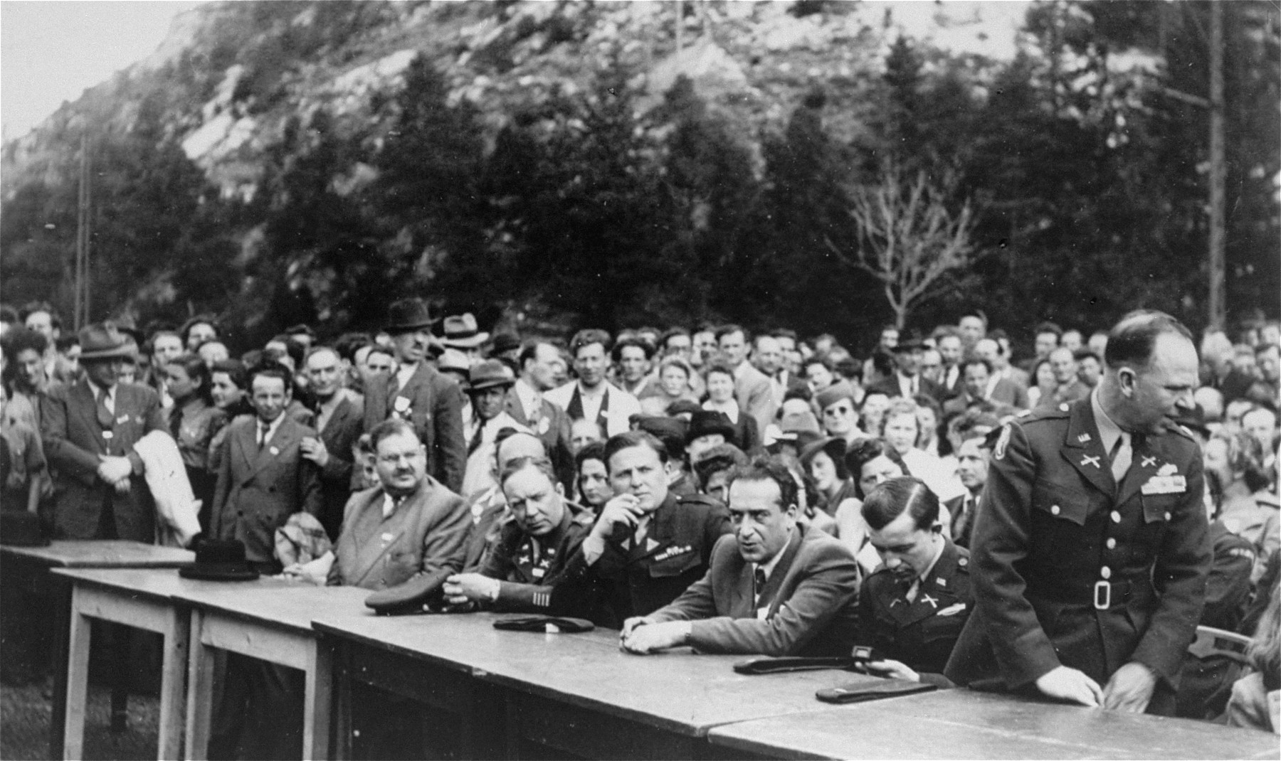 American and German officials participate at an outdoor meeting of Jewish DPs in the American Zone of Germany held in the Mittenwald displaced persons camp to commemorate the death march from Dachau to Tyrol.
