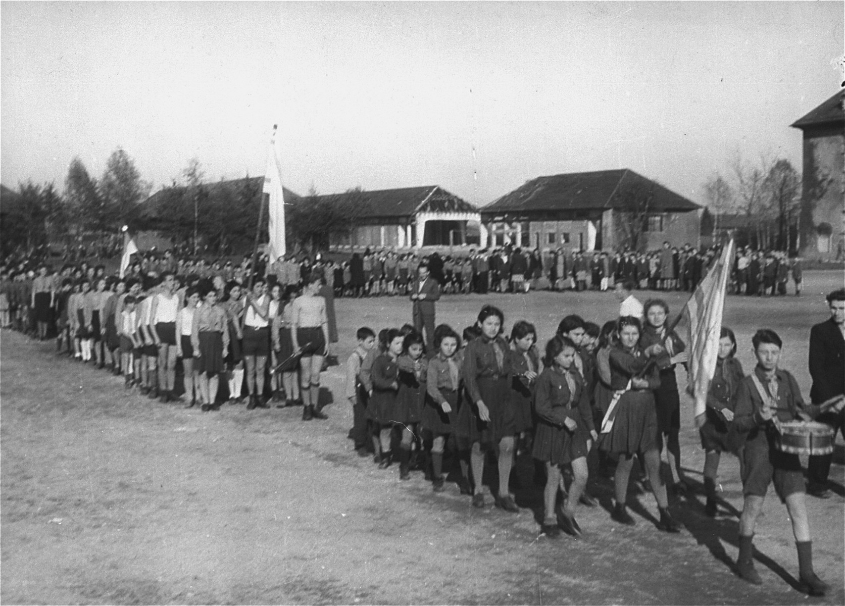 Zionist youth parade with flags around the central yard in the Landsberg displaced persons'camp.