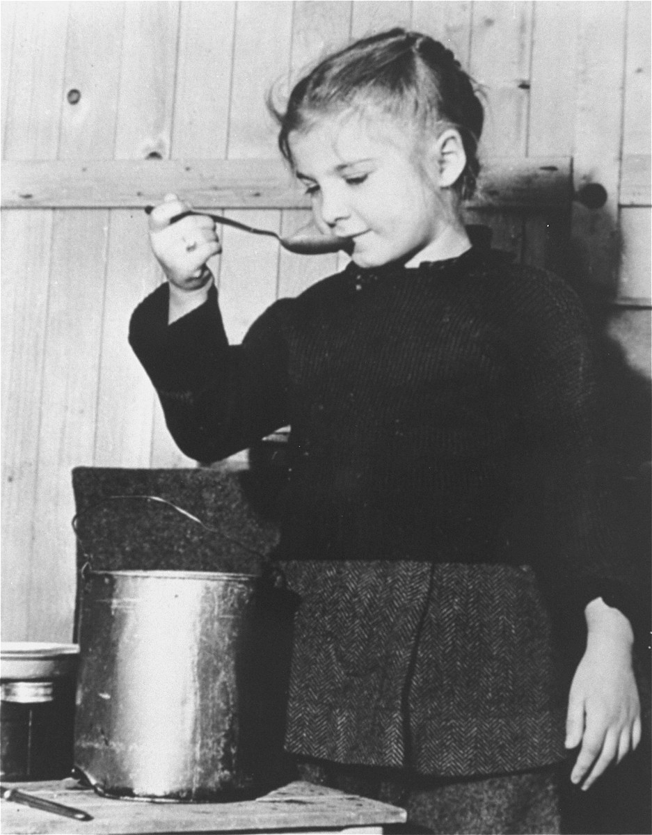 A young girl ieats from a lunch pail at an unidentified displaced persons camp near Munich.