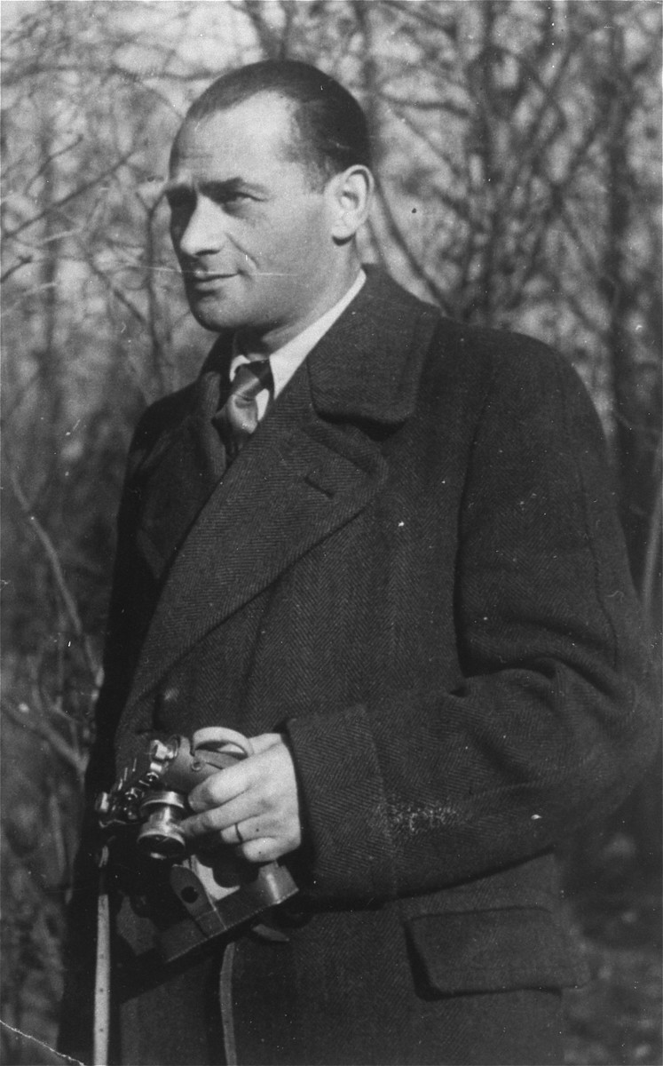 Portrait of Mendel Rozenblit holding a camera while living as a displaced person in Munich.